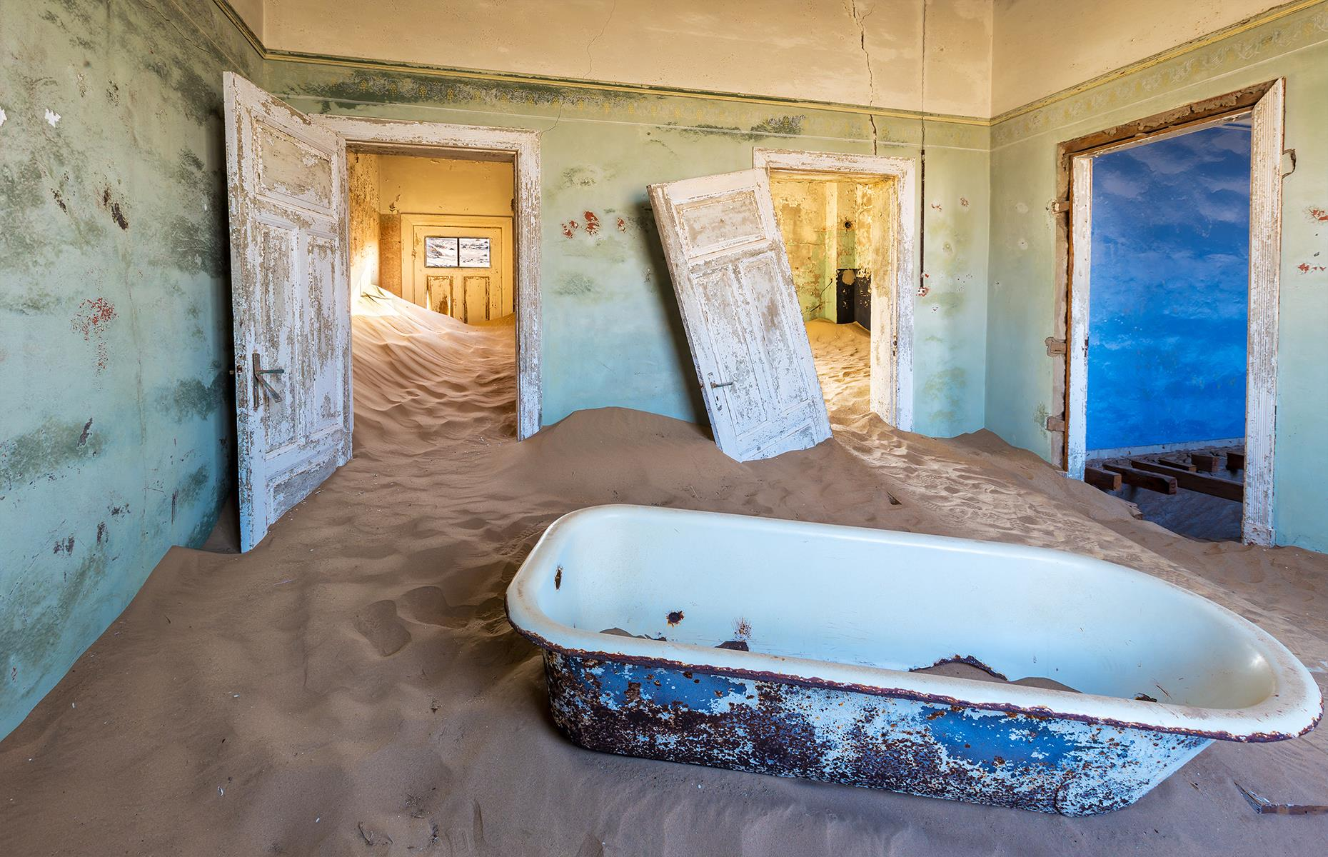 Slide 59 of 68: Then in 1928, a far bigger diamond deposit was discovered south of Kolmanskop, and many of the inhabitants left in their search for treasure. By 1956, the town was completely abandoned and, today, the shifting red desert sands sweep into the decrepit houses.