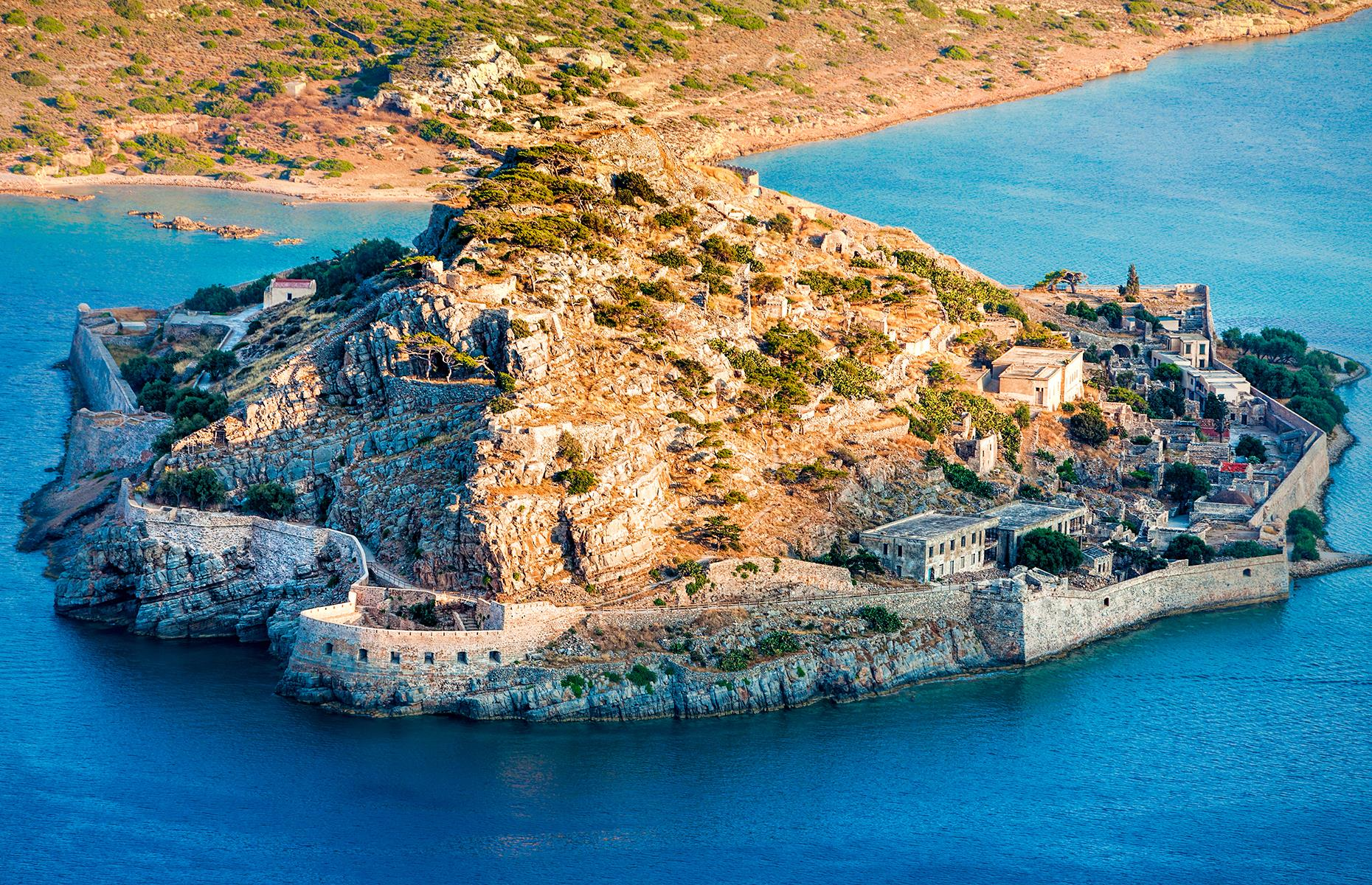Slide 16 of 68: Located in northeastern Crete, Spinalonga wasn't always an island – during Venetian occupation the coast was carved out for defensive purposes and a fort was built. In 1715, the Ottoman Turks took over the Venetian rule until the Cretan revolt at the end of the 19th century.