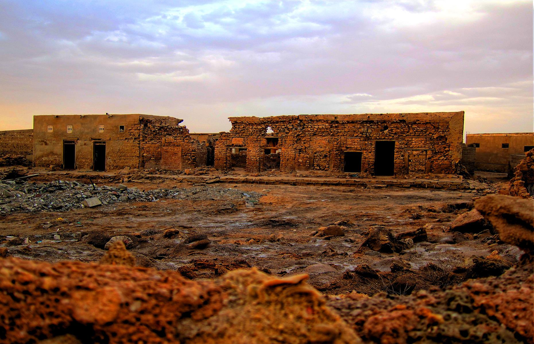 Slide 34 of 68: Now the coral stone buildings lie empty, coated in grains of rusty red desert sand. Some doors are locked, but visitors can peer into the belly of the buildings to see abandoned classrooms and bedrooms. The mosque still stands too. Take a look at more secret wonders hidden in the world's largest deserts.