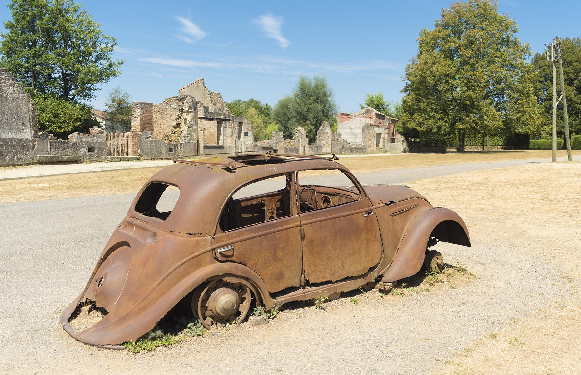 Slide 45 of 68: Today, Oradour-sur-Glane is a memorial to those who perished. Rusted cars, including the Peugeot 202 the mayor drove before his brutal death, still sit on the roads, while sewing machines, pitchers and pans still lie scattered where they were on that fateful day.