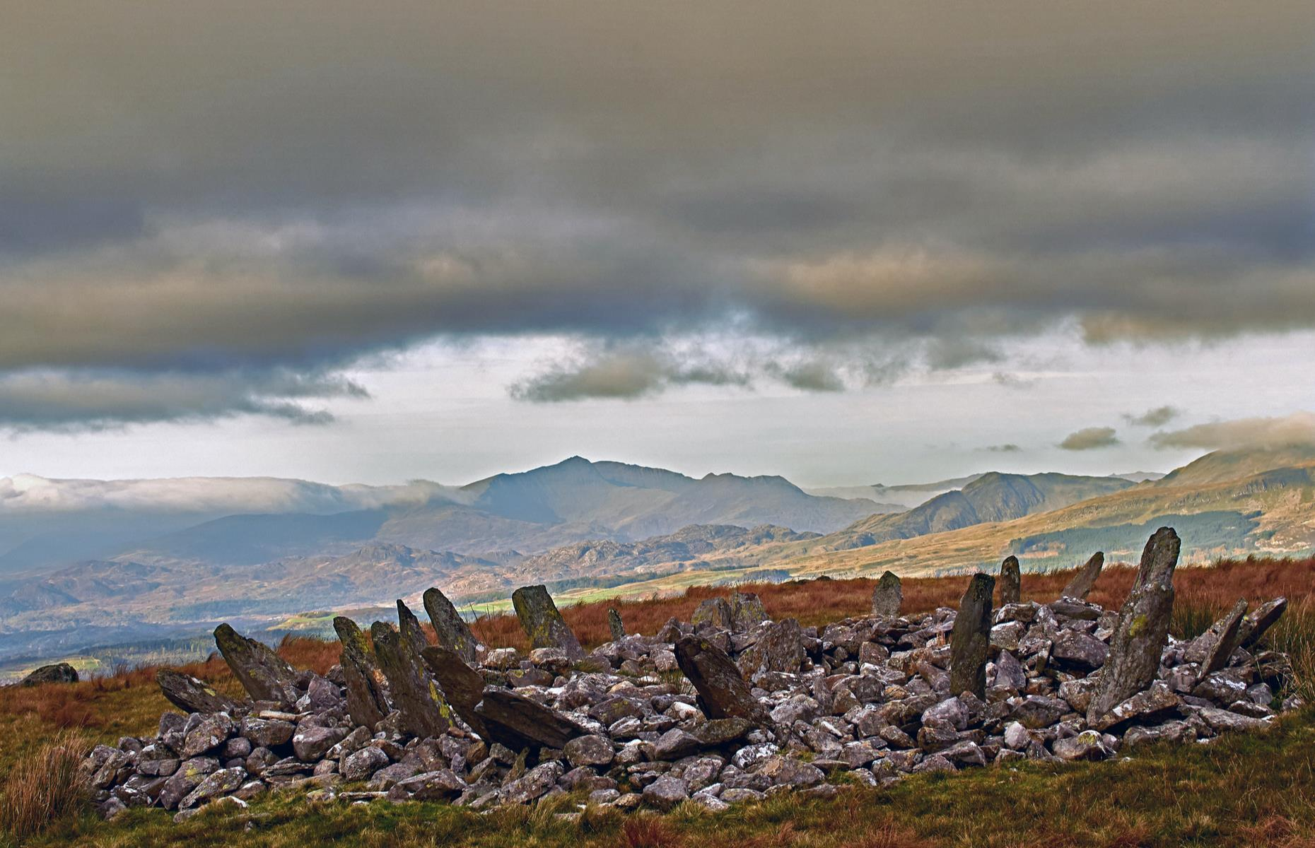 """Slide 18 of 31: The Bronze Age ring cairn of Bryn Cader Faner would once have marked a burial site. With its name translating as """"the hill crowned with the throne of the flag jagged slate"""", the spiky structure is an arresting sight amid a lonely patch of moorland in the brooding hills of Snowdonia. The 4,000-year-old formation has around 15 long, thin stone slabs of slate that lean outwards, reminiscent of a crown of thorns. Find more reasons to love Wales here."""