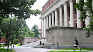 a group of people walking on a sidewalk: A view of Harvard Yard on the campus of Harvard University on July 08, 2020 in Cambridge, Massachusetts. Harvard and Massachusetts Institute of Technology have sued the Trump administration for its decision to strip international college students of their visas if all of their courses are held online.