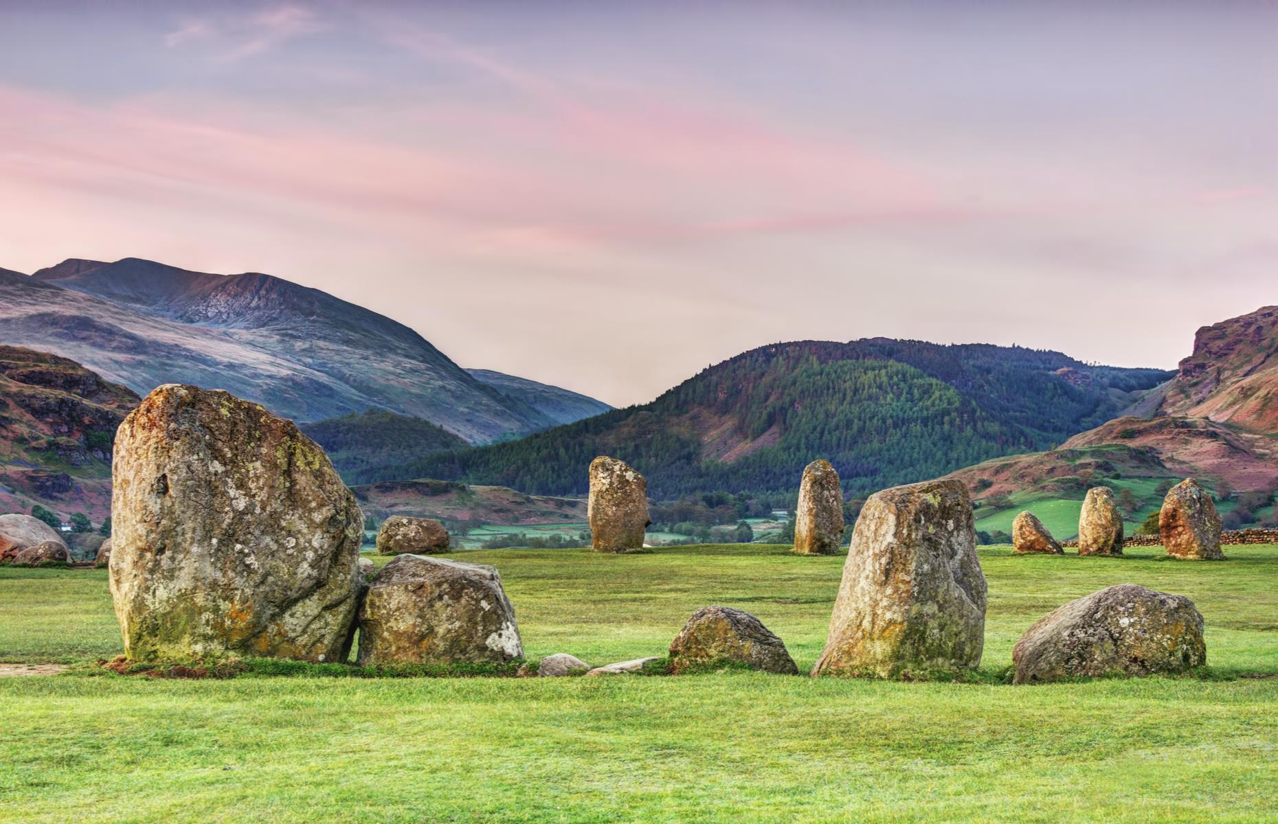 Slide 5 of 31: One of Britain's most ancient circles, Castlerigg, sits high in the fells of Cumbria – a suitably beguiling setting for such a mystical place. The ring of 38 stones is encircled with the brooding forms of Skiddaw, Blencathra, Castlerigg Fell, High Rigg and Clough Head. It was erected by Neolithic farming communities around 4,500 years ago, possibly as a meeting place.