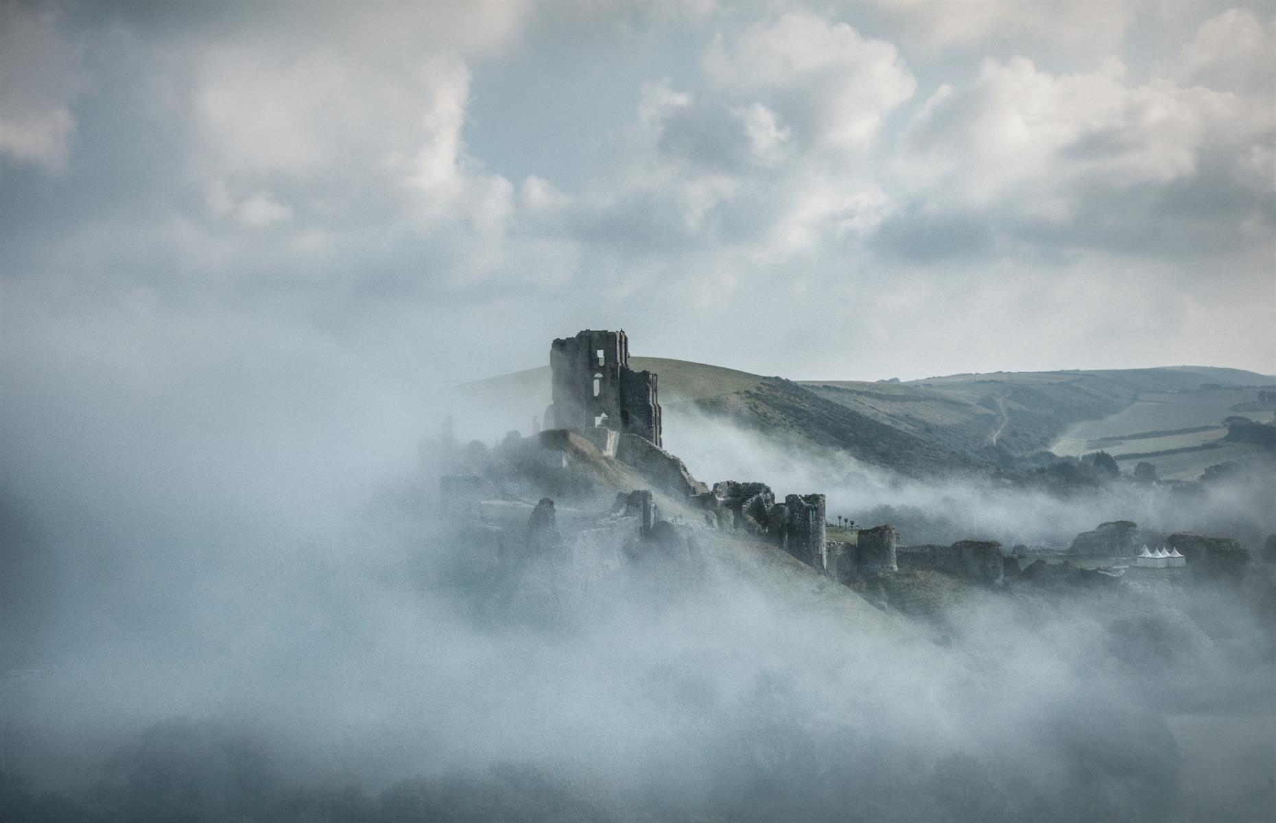 Slide 2 of 29: Corfe Castle, on the Isle of Purbeck in Dorset, has been a romantic ruin on the English landscape for 350 years. Built by William the Conqueror in the early 12th century, it's seen its share of horror. In the 13th century, Bad King John lived up to his name when he starved 22 Frenchmen to death in the dungeons. In 1572, Queen Elizabeth I sold the castle into private hands and it was bought by Sir John Bankes in 1635.