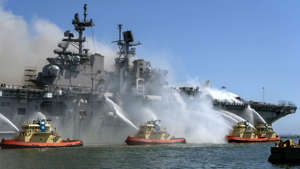 a small boat in a body of water with smoke coming out of it: Navy to scrap USS Bonhomme Richard after days-long fire