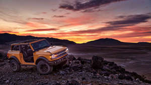 a car parked in the desert: 2021 Ford Bronco off-road at sunset