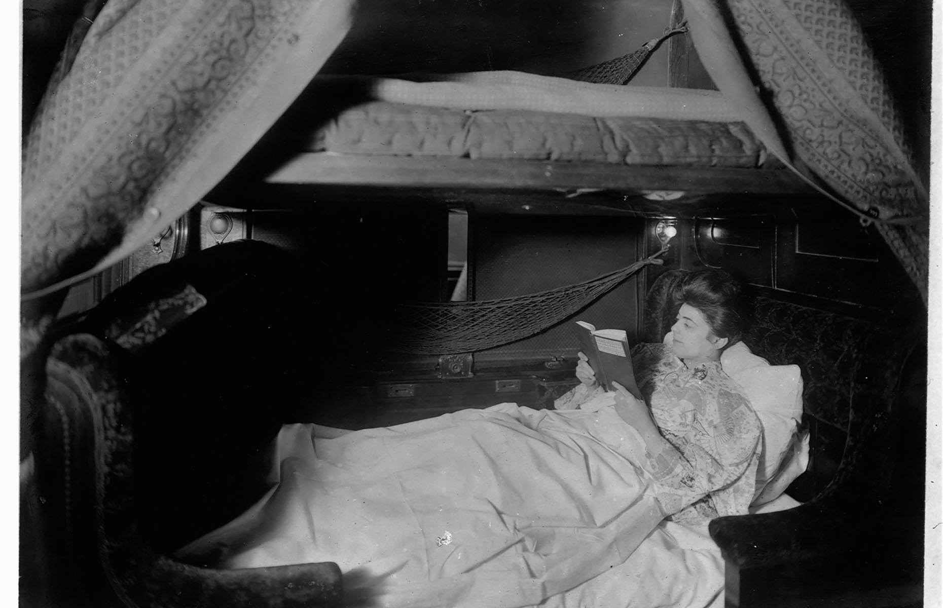 Slide 8 of 32: While train travel was still considered a luxury, especially for the wealthier passengers, rather than just a mode of transport, comfort was a priority. Photographed in 1905, this woman is enjoying reading a book before bed in her spacious bunk on a sleeping car.