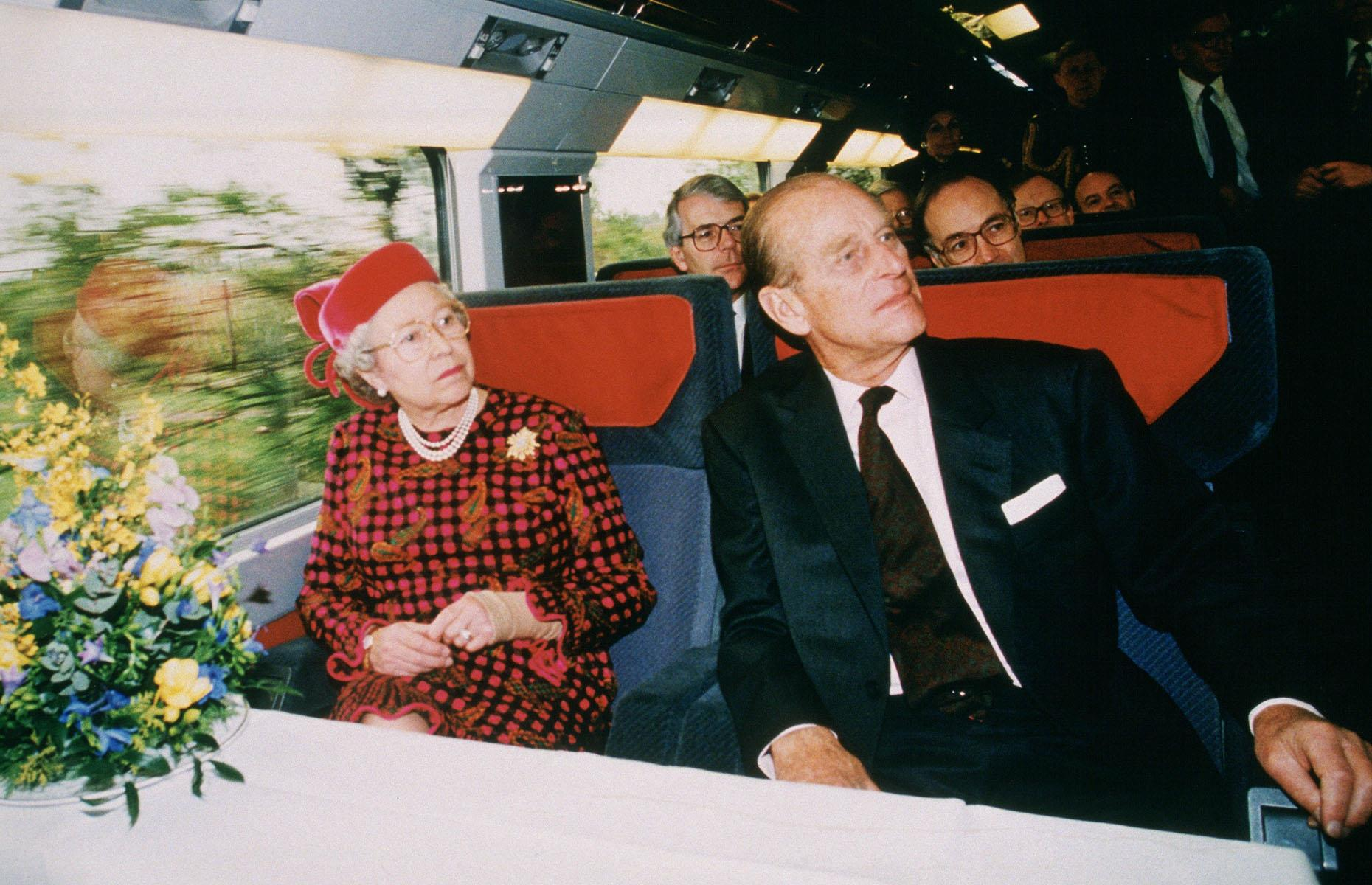 Slide 30 of 32: The dream of a tunnel and a train connecting mainland Europe and the UK finally came true in 1994 when both the Eurotunnel and Eurostar were launched. Here, Queen Elizabeth II and Prince Philip are joined by Prime Minister John Major (sitting behind the Queen) aboard a Eurostar train on the inauguration of the tunnel on 6 May 1994.