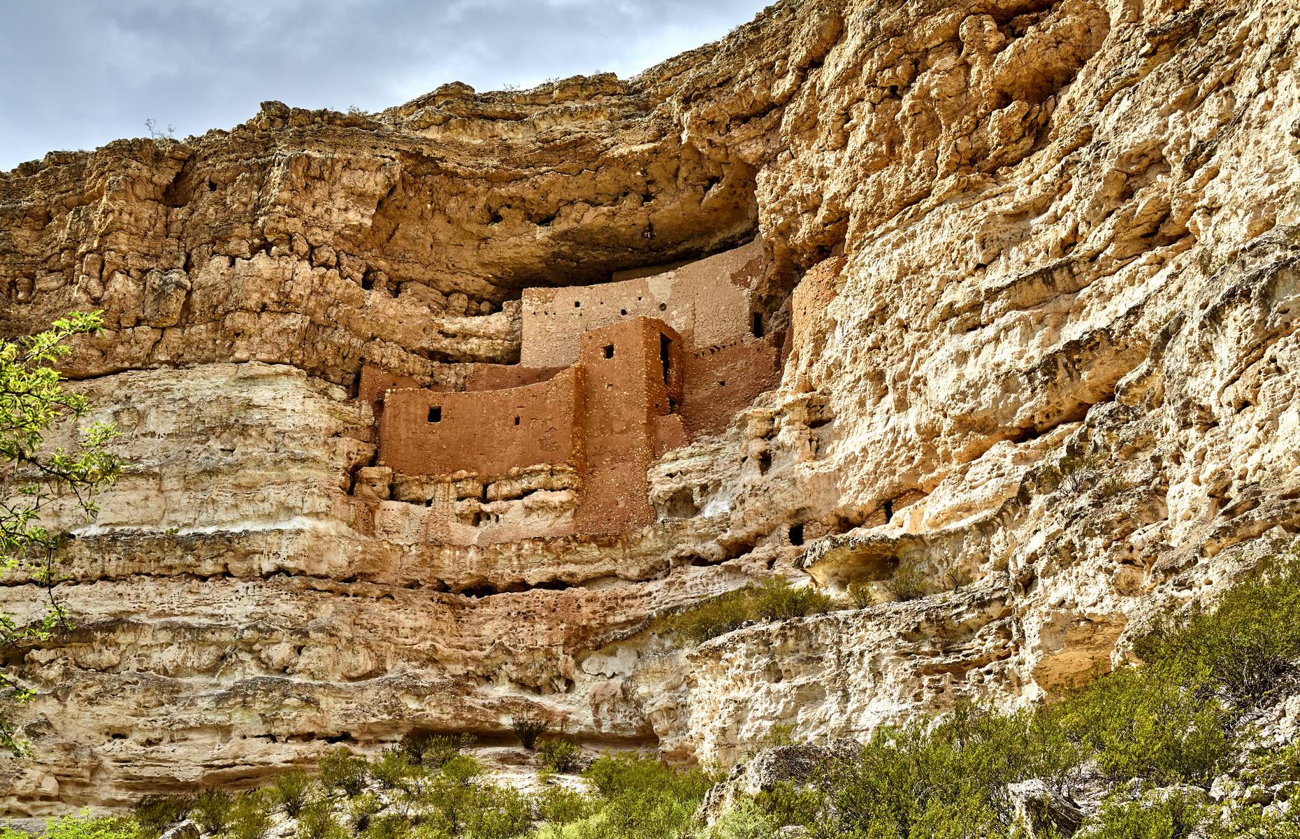 Slide 19 of 27: Locations don't come much more impressive than the perch occupied by this high-rise building, tucked into limestone cliffs in the desert of Camp Verde. Montezuma Castle was built and occupied by the Sinagua people between AD 1100 and 1425, and used as an abode with 20 rooms.