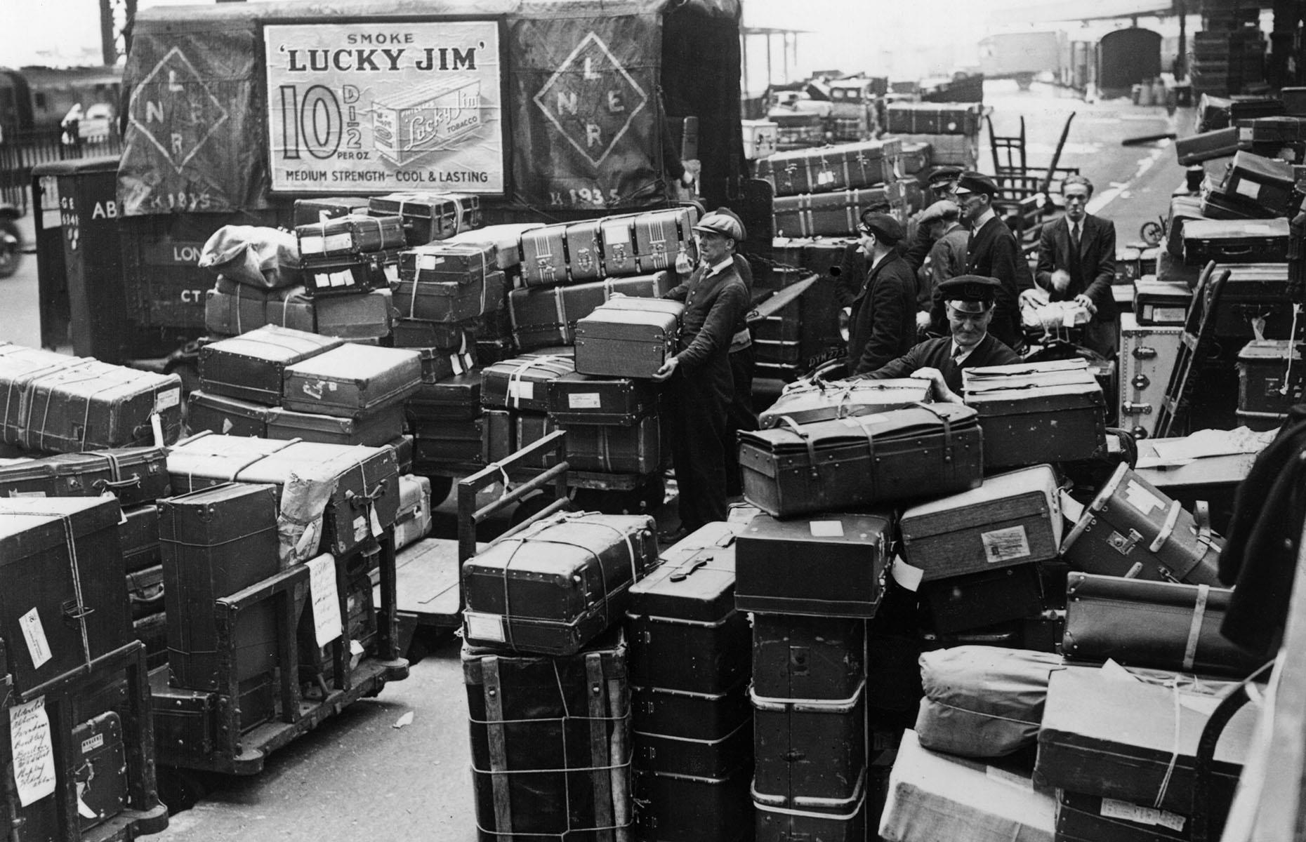 Slide 18 of 32: Whether it's train travel in the 1930s or jetting away on an airplane in the 2000s, there's still baggage to be loaded and unloaded. Here baggage men unload passengers' suitcases from a train that's arrived at London Waterloo station. Take a look at how air travel has changed in the last 100 years.
