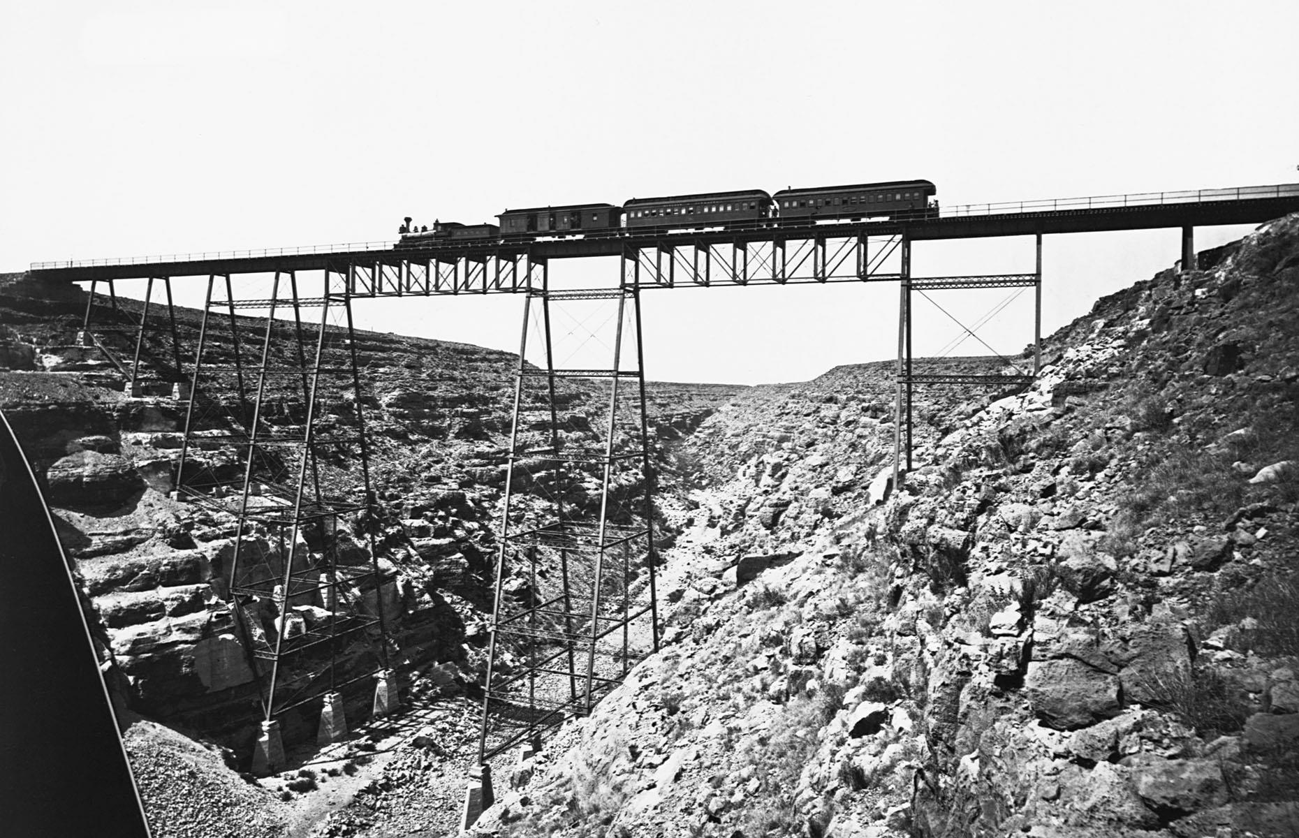 Slide 3 of 32: One of the biggest obstacles railroads faced in the early days was traversing the often challenging landscapes. One such place was Canyon Diablo in Arizona – this is the earliest inception of a railroad bridge across the canyon photographed at some point in the 1870s. The current steel bridge was finished in 1903, but the foundations of the original trestle bridge can still be seen today.