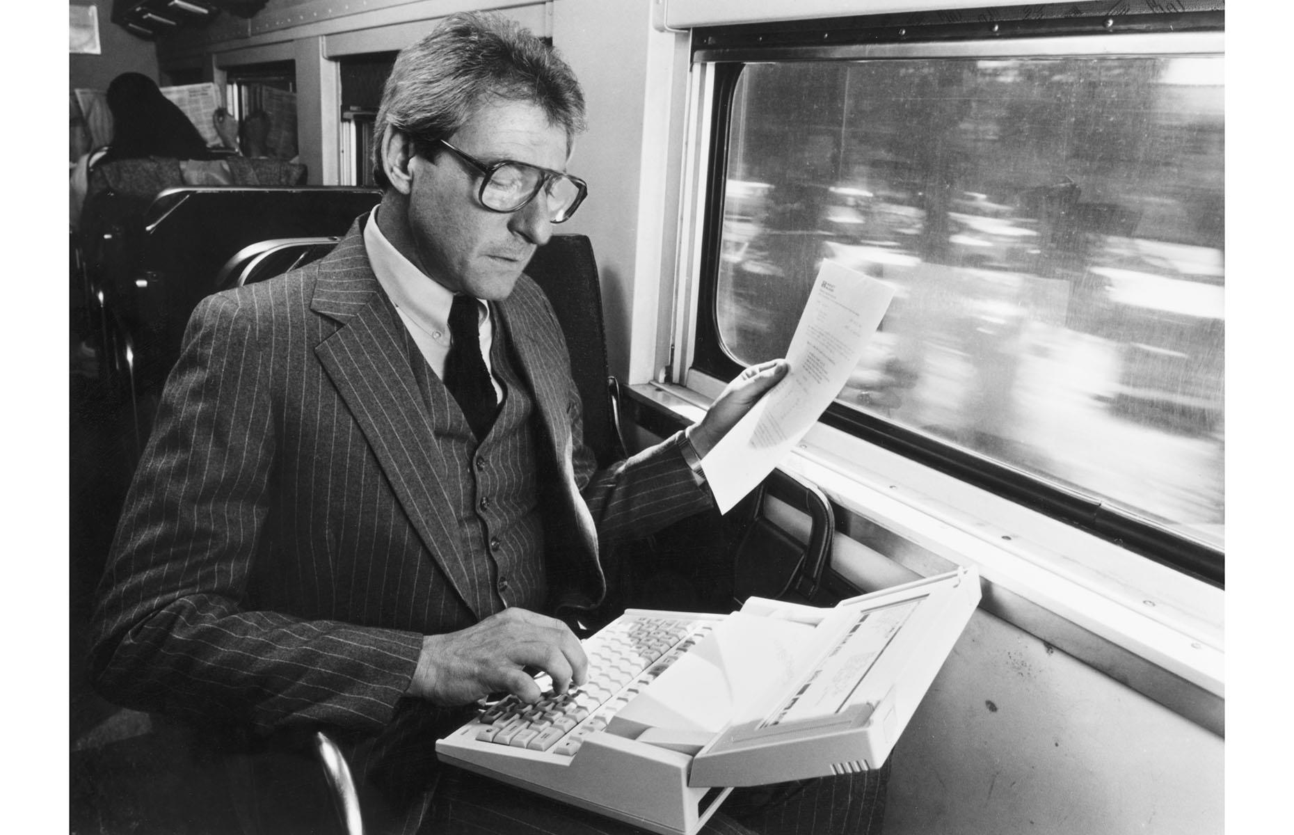 Slide 28 of 32: Not at all a surprising sight on any train today, this gentleman from the 1980s is well ahead of his time as he's using precious commute time to do work on an early Hewlett-Packard laptop. Discover vintage photos of American summer vacations.