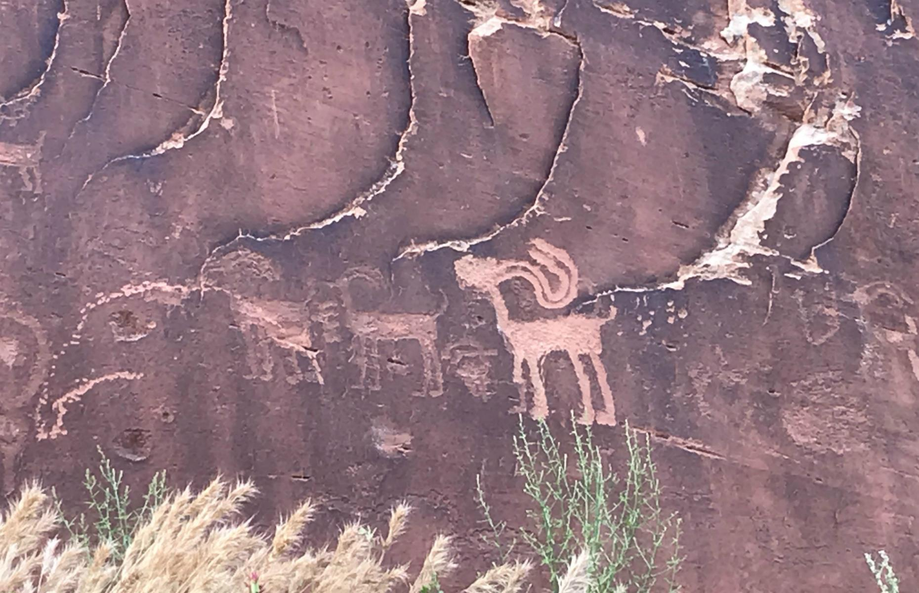 Slide 5 of 27: The early desert dwelling is made up of a series of well-preserved rooms, some arranged over two stories, tucked beneath apricot-hued cliffs. There are hundreds of petroglyphs (carved rock art), including an image of Kokopelli, a fertility deity and trickster god depicted with a flute and feathered headdress.
