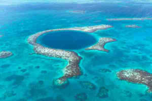 a body of water with Great Blue Hole in the background: One of the most famous diving spots in the world is Belize's Blue Hole. (Photo via Shutterstock)