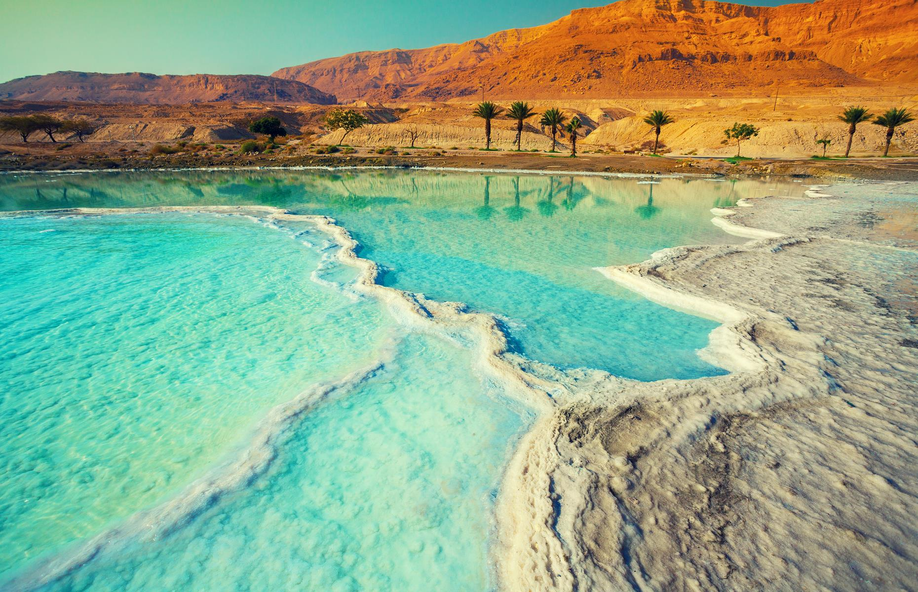 Slide 20 of 37: Bordered by Jordan and Israel, the landlocked Dead Sea is the lowest body of water on Earth. The high concentration of salt in the water means that bathers can naturally float in it. However, the sea's waters are now receding and this is causing sinkholes to appear.