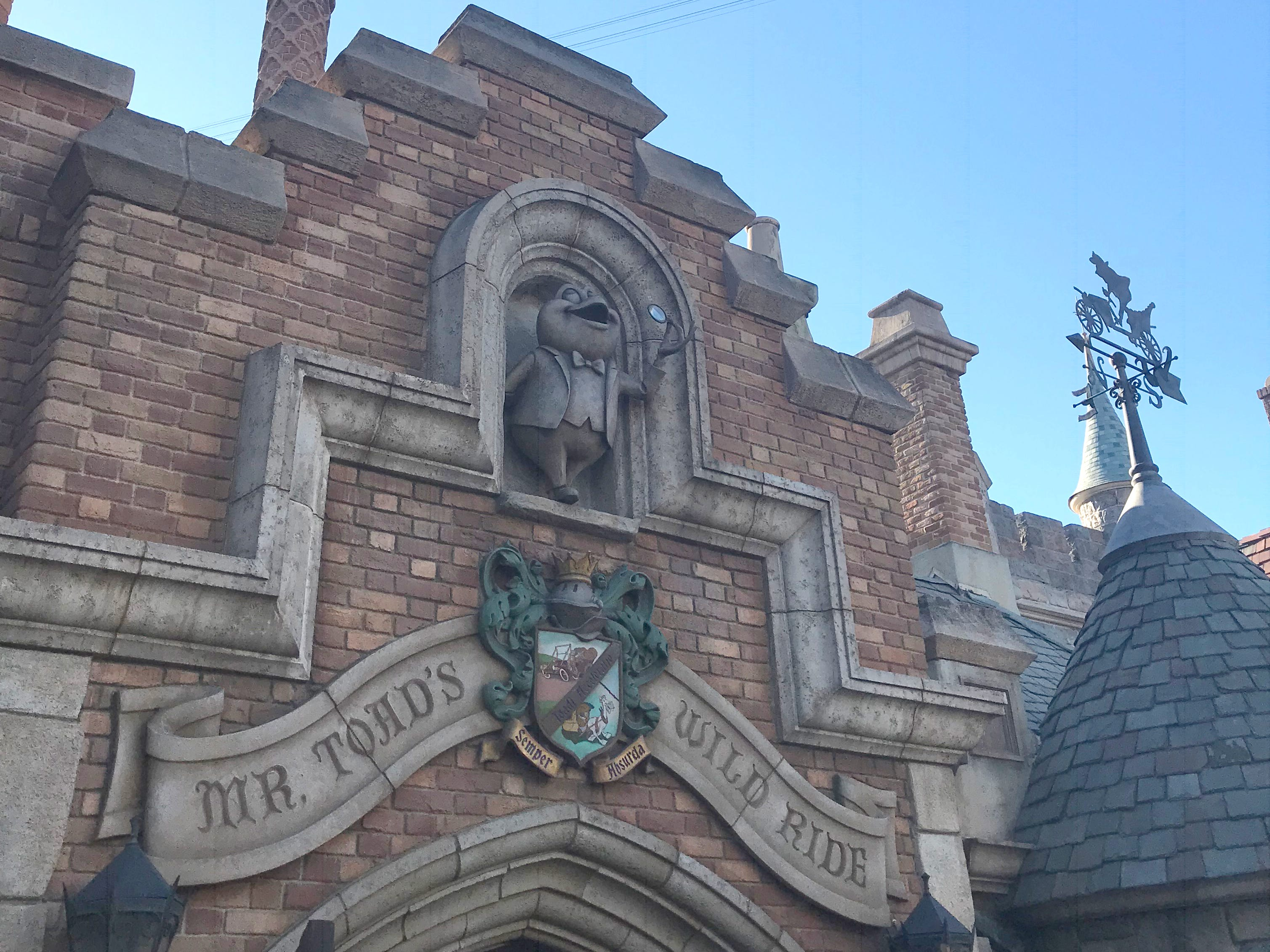 """Slide 17 of 23: You'll see Mr. Toad's family crest on the outside of the building that houses Mr. Toad's Wild Ride. It reads """"Toadi Acceleratio Semper Absurda"""" in Latin, which roughly translates to """"The acceleration of Toad is always absurd."""""""