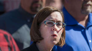 a close up of Kate Brown wearing glasses: Oregon governor urges hosts to 'uninvite' guests