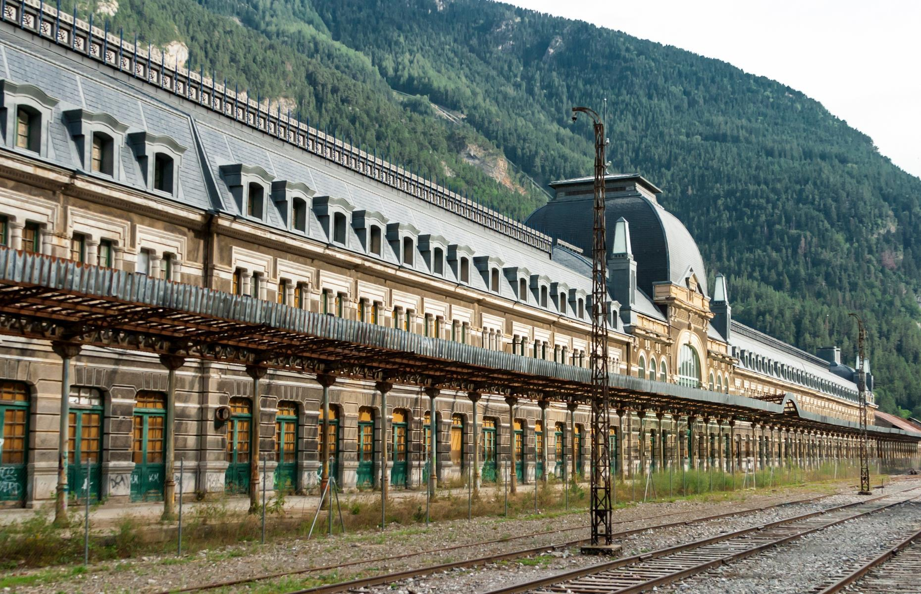 Slide 31 of 33: Once the second biggest train station in Europe, Canfranc International Railway Station sits high in the Pyrenees mountains in a small Spanish village on the border with France. It was jointly owned by the two countries and much celebrated, until it was beset by financial troubles and war. The station finally closed in the 1970s after a train derailed, crashing into a bridge. The opulent building was left to slowly decay.