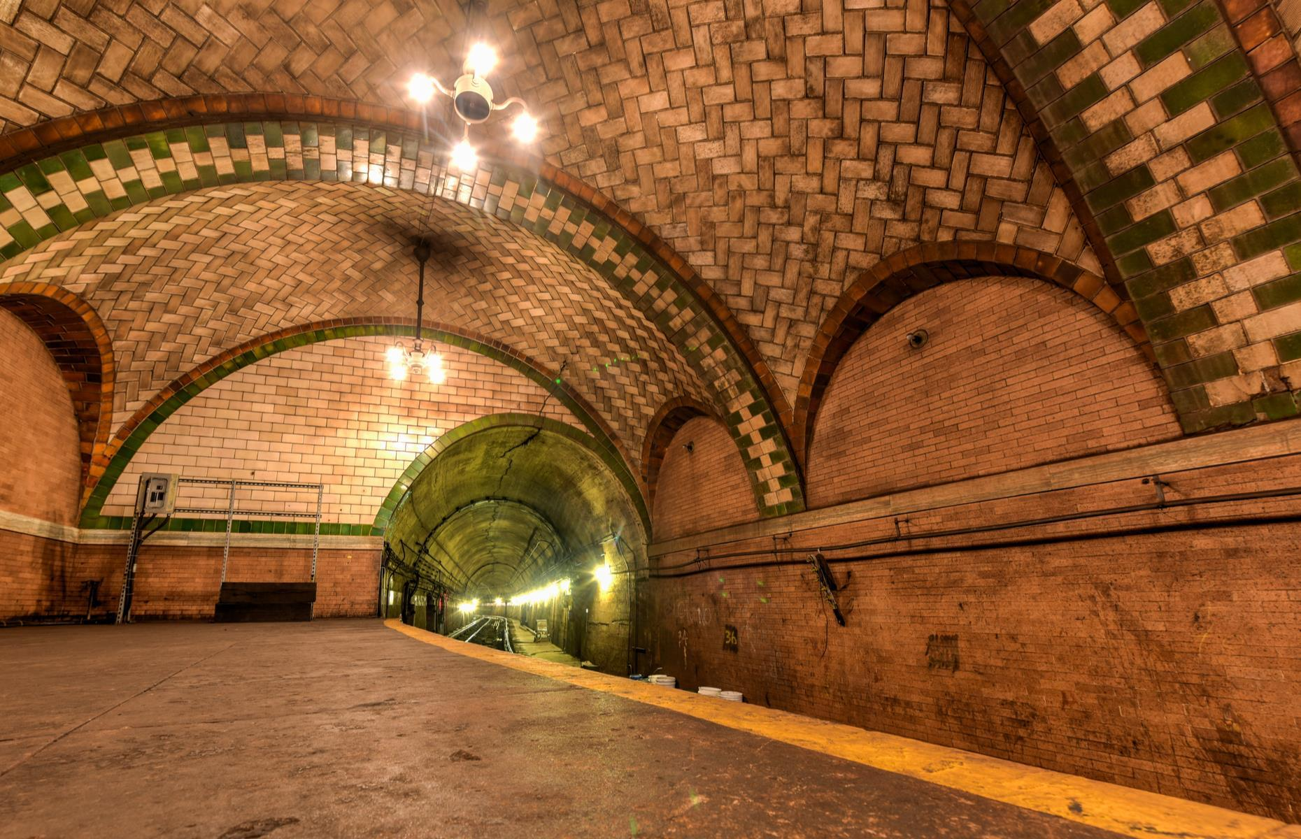 Slide 26 of 33: With its curved platform, vaulted tile ceilings, skylights, and chandeliers still largely intact, the station may have been abandoned, but it remains a vital piece of America's rail history. Its track is still used as a turnaround spot for the 6 line, but the station is closed off to the public. However, members of The New York City Transit Museum can usually book into the semi-regular guided tours it runs into the abandoned station.