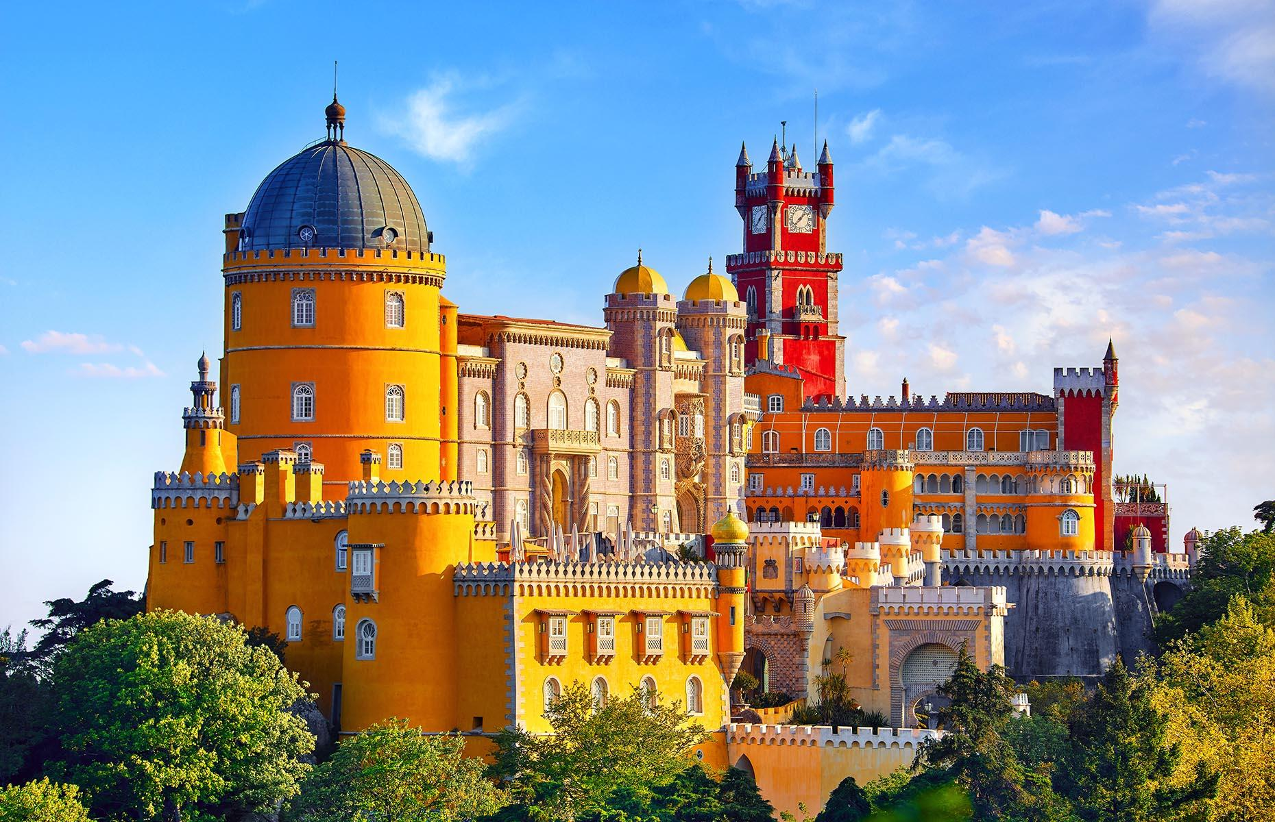 Slide 26 of 61: It might be called a palace, but it is in fact a castle, and few are so heart-flutteringly pretty as Pena Palace, whose butter-yellow turrets and brick-red towers rise above the treetops in hilly Sintra, just outside Lisbon. The multicolored beauty, an example of 19th-century Romanticism, was commissioned by King Ferdinand II and completed in 1854, and has been home to Portuguese royals through the years.