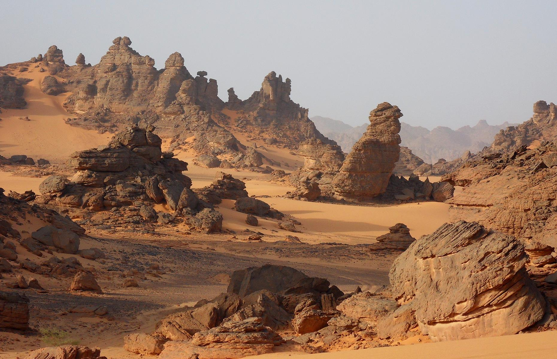 Slide 30 of 44: The Ennedi Plateau is essentially a natural bulwark, with towering rock buttresses, bridges and arches. Sandstone bluffs here soar above 4,756 feet (1,450m) and the stark, otherworldly landscape looks like something straight from a Star Wars film.