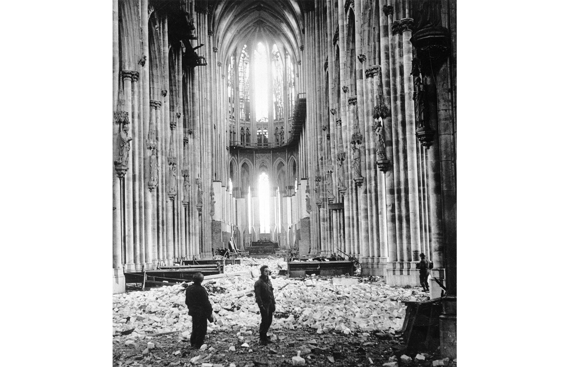 Slide 12 of 32: Cologne Cathedral dates rightback to the 13th century, although much of it was constructed during the 1800s.But the striking sacred building almost didn't survive the 20th century.Cologne was hit hard in the Second World War, with buildings razed to the ground and the city centerdevastated. The cathedral wasn't sparedeither.It's thought it took 14 bomb hits during the war, its lofty spires a useful reference point for the Allied Forces. Here US soldiers stand among the rubble in 1945, with sizeable holes in the vaulted ceiling.