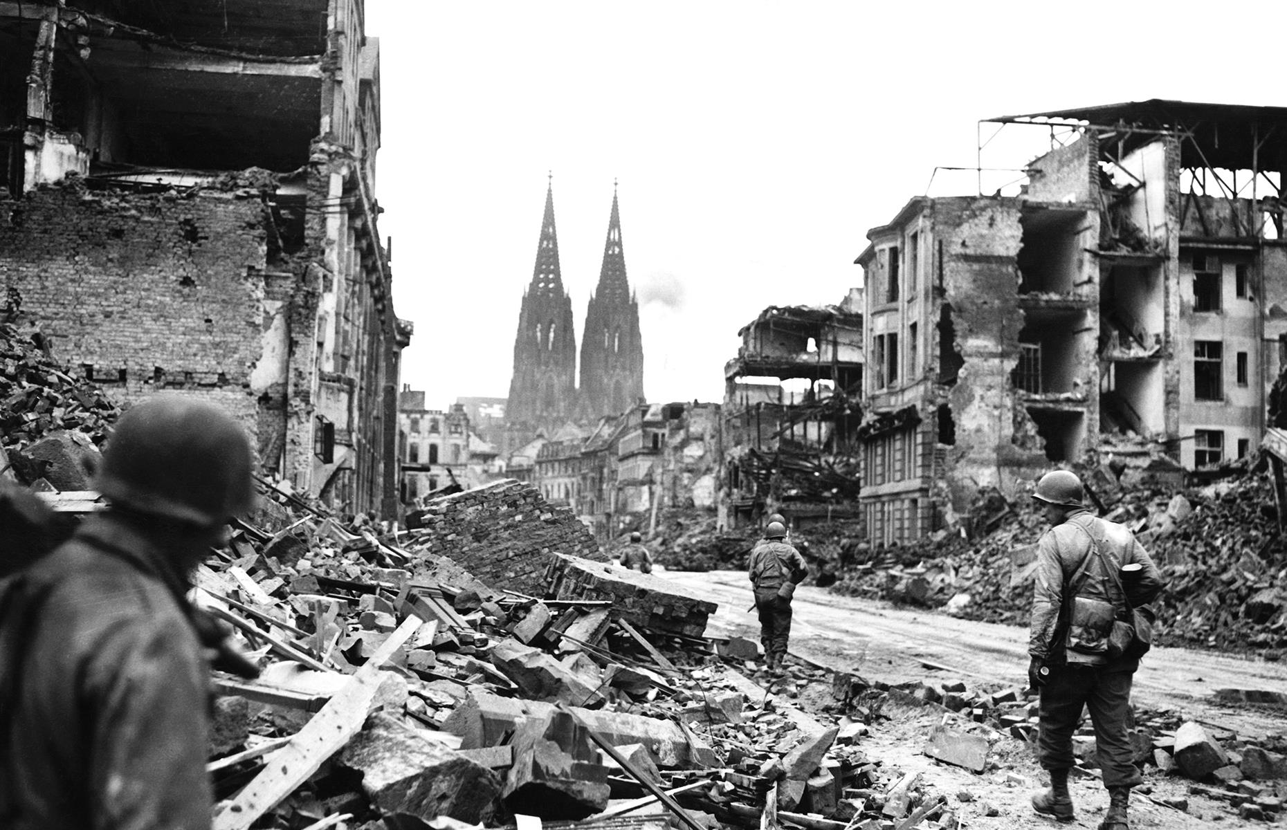 Slide 13 of 32: Although the cathedral suffered extensive damage – including holes in its walls and spires, and shattered stained glass – it remained standing. In this striking image, the cathedral is seen brooding over the flattened city in 1945 as US troops move through the ruins.