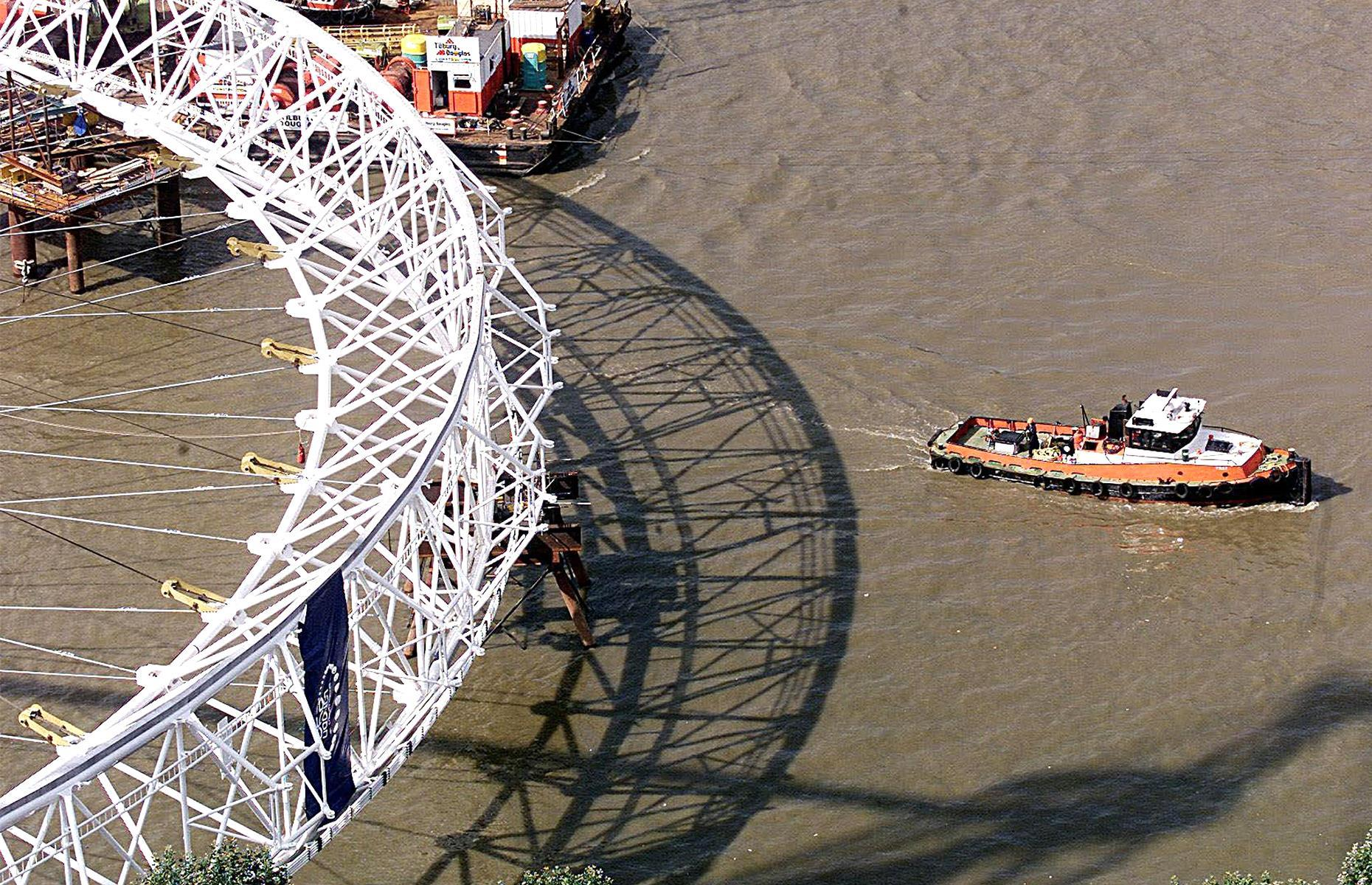 Slide 2 of 32: The London Eye was dreamt up in the 1990s by husband-and-wife architect team David Marks and Julia Barfield as part of a competition for a monument to mark the millennium. The competition ultimately didn't result in anything, but the Barfields decided to take the project forwards themselves. Construction of the now-famous London landmark began in 1998 and it's pictured here in 1999, laying horizontally across the River Thames ready to be lifted into position.