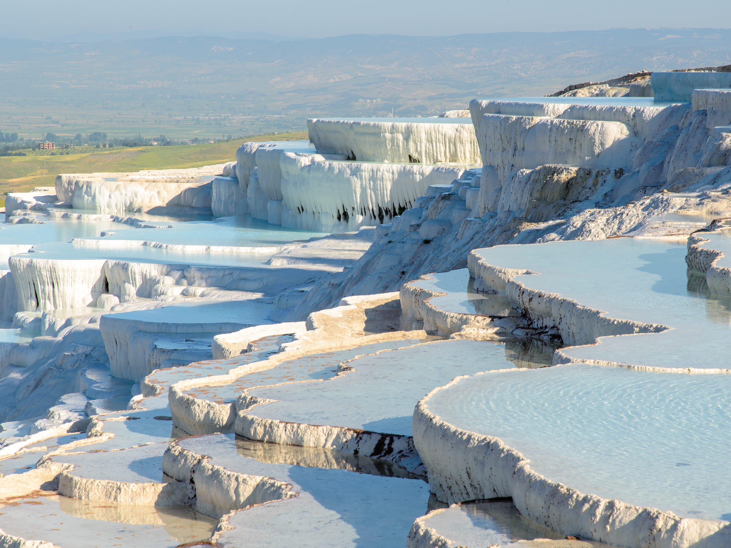"""Slide 14 of 51: Known as """"cotton castle"""" in Turkish, the bleached white, travertine terraces hold warm water pooled from natural hot springs. The terraces were created over time by limestone mineral deposits from geothermal activity."""