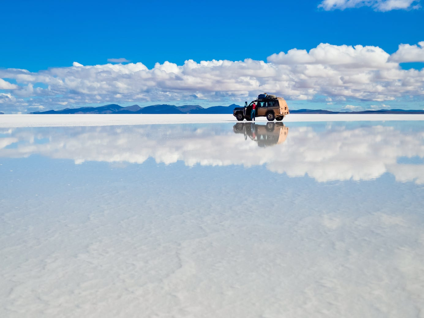 Slide 24 of 51: When lakes near these Bolivian salt flats overflow, they create a majestic mirrored surface that reflects the sky and clouds above. TheSalar de Uyuni are the largest of their kind and cover a whopping 4,050 square miles of the Bolivian Altiplano.The vast oasis of salt boasts a horizon that never seems to end, making this spot a photographer's dream.