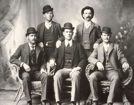 """Slide 11 of 32: Harry A. Longabaugh adopted the nickname the """"Sundance Kid"""" in jail after stealing a horse from a ranch in Sundance, Wyoming. He met Butch Cassidy in 1896. The pair would later carry out a string of successful bank and train robberies while riding with the """"Wild Bunch."""" With lawmen on their trail, they fled together to South America, where they were allegedly killed in a shootout in Bolivia. Pictured is the """"Wild Bunch."""" Front row, left to right: Harry A. Longabaugh, Ben Kilpatrick, Robert Leroy Parker. Standing: Will Carver and Harvey Logan."""