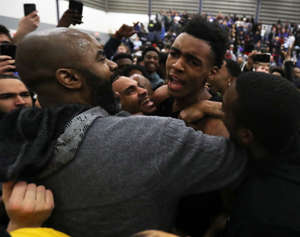 a group of people in front of a crowd: Ypsilanti Lincoln high school's Emoni Bates celebrates with his dad after the 81-79 win against Novi Detroit Catholic Central high school in the regional final Thursday, March 7, 2019 at Ypsilanti Lincoln high school in Ypsilanti, Mich.