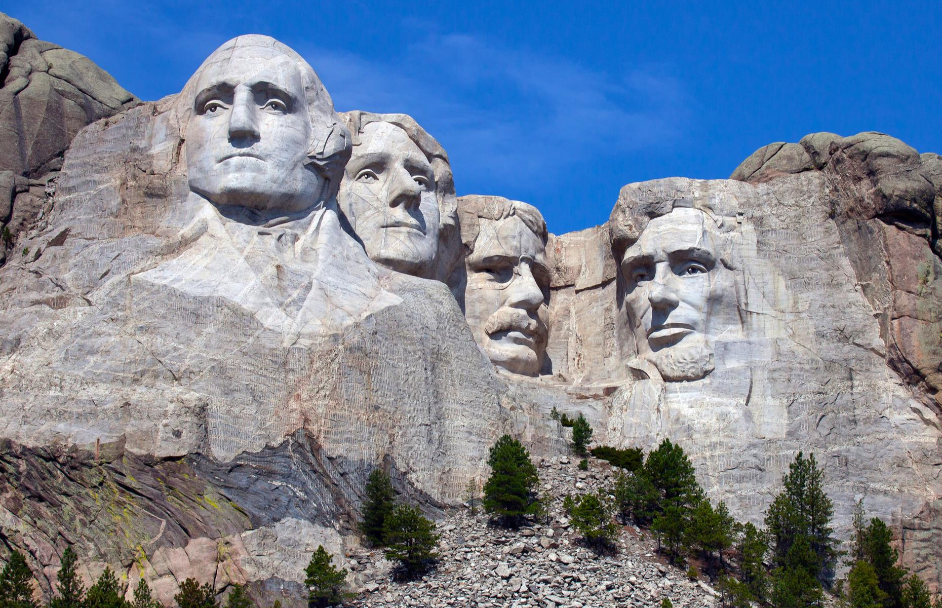 Slide 39 of 51: The 60-foot (18m) tall faces of four American presidents (George Washington, Thomas Jefferson, Theodore Roosevelt and Abraham Lincoln) stare out from the granite rock faces of the Black Hills in Keystone. Almost three million visitors usually come to gaze upon the presidents every year but the site is not without controversy. The Black Hills is considered sacred ground for indigenous people and this area was taken from them by the government after a series of bloody battles.