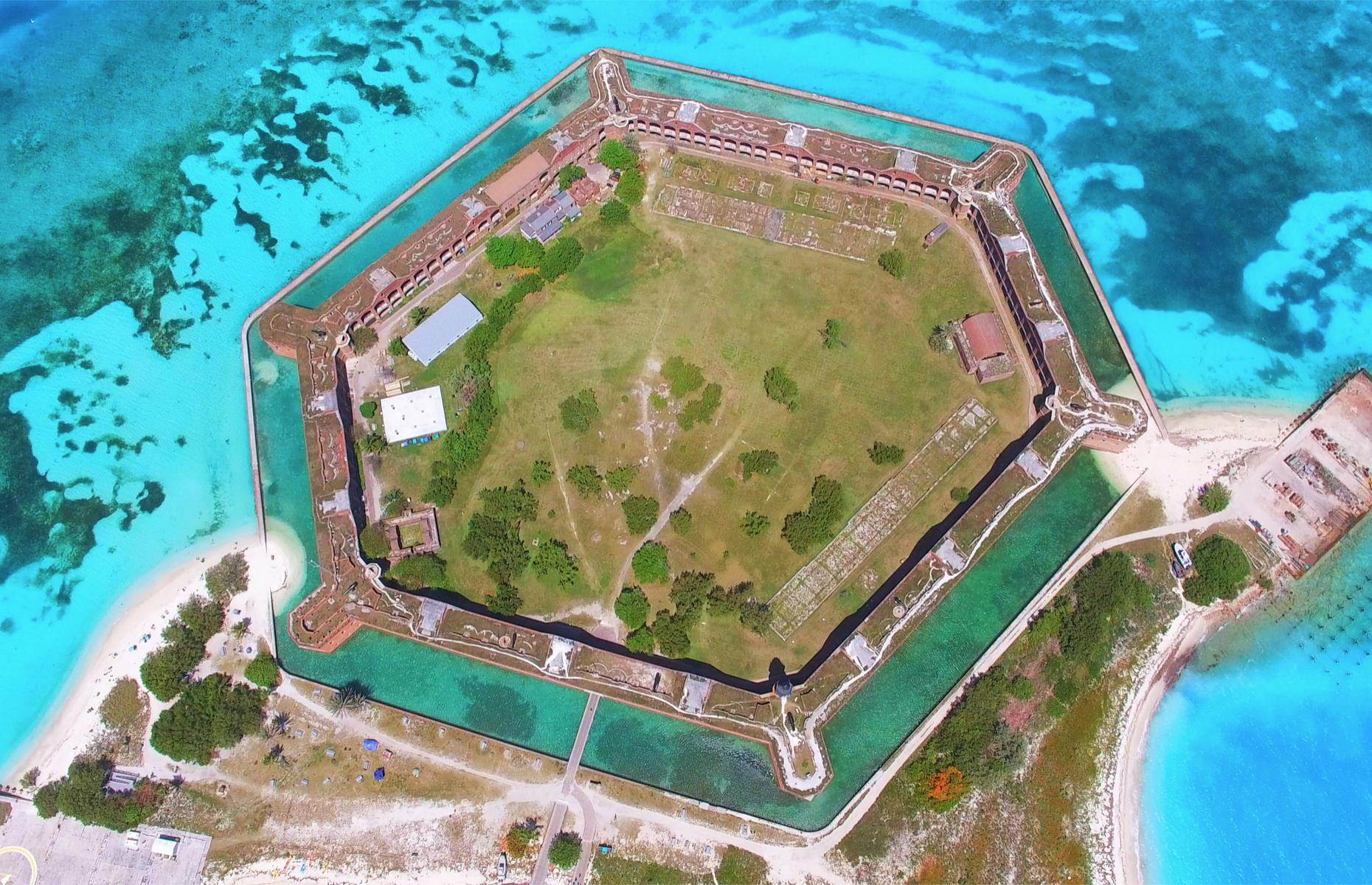 Slide 25 of 51: An unfinished hexagonal fortress in the waters of the Dry Tortugas National Park, Fort Jefferson was intended to protect a deep-water anchorage in the Florida Strait when construction began in 1846. Later, the fort became a military prison but was eventually abandoned. Visitors can usually take a low-altitude flight or ferry out to the bastion, and explore the marine life-filled waters and beaches surrounding it. Check drytortugas.com for updates and current availability.
