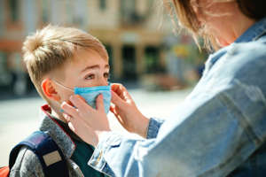 a close up of a person talking on a cell phone: Mother puts a safety mask on her son's face.