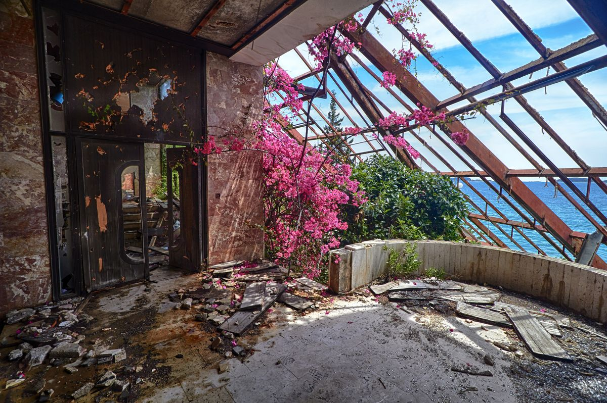 Slide 6 of 38: Bougainvillea and the Adriatic sea rule in this abandoned hotel on the Croatian coast. Hotel Goricina was once a luxe hotel in a Yugoslavian military resort, which was destroyed in the Croatian War of Independence, along with a string of other hotels.