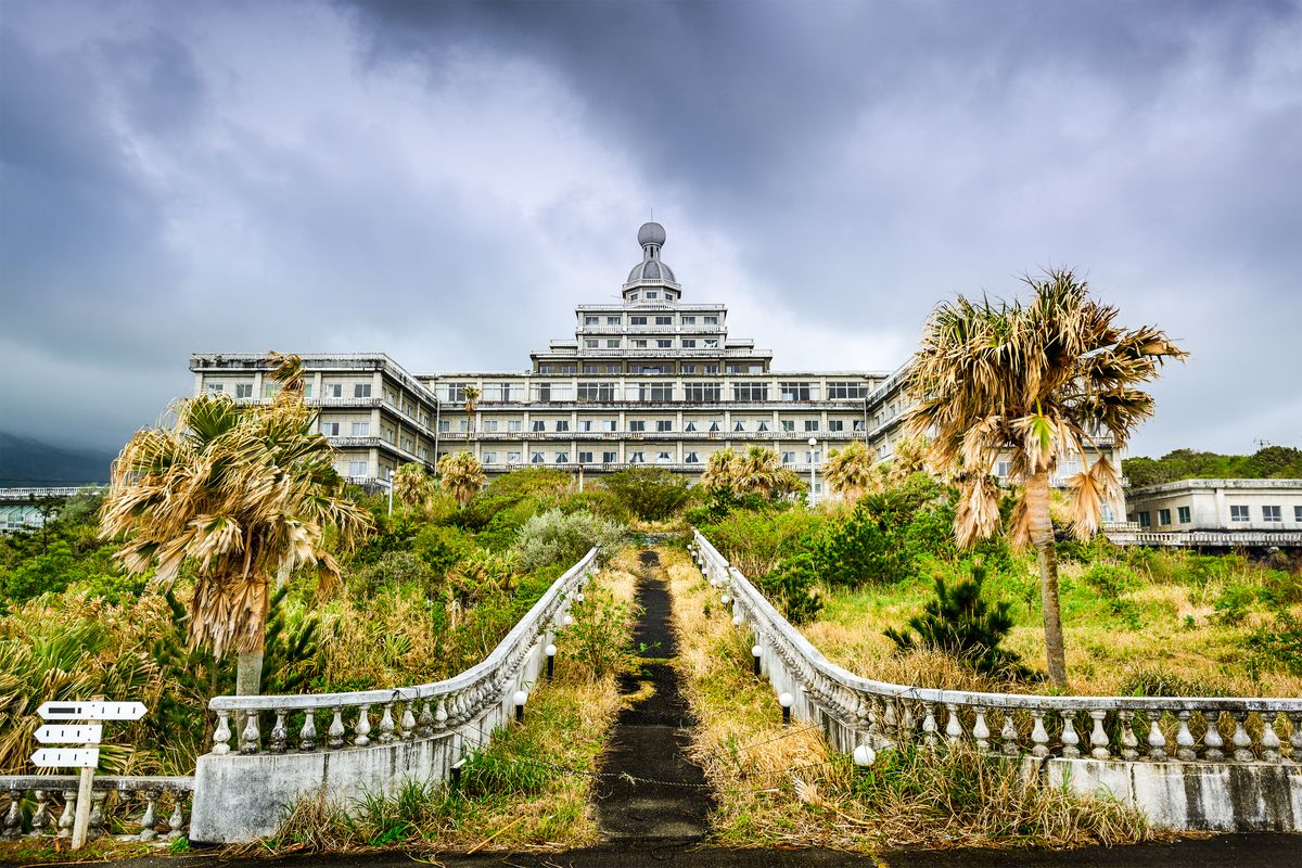 Slide 7 of 38: Located on the lush Japanese island of Hachijojima, Hachijo Royal Hotel was once one of the country's largest resorts. The French Baroque architecture juxtaposed against the moss and overgrown trees is eerie.