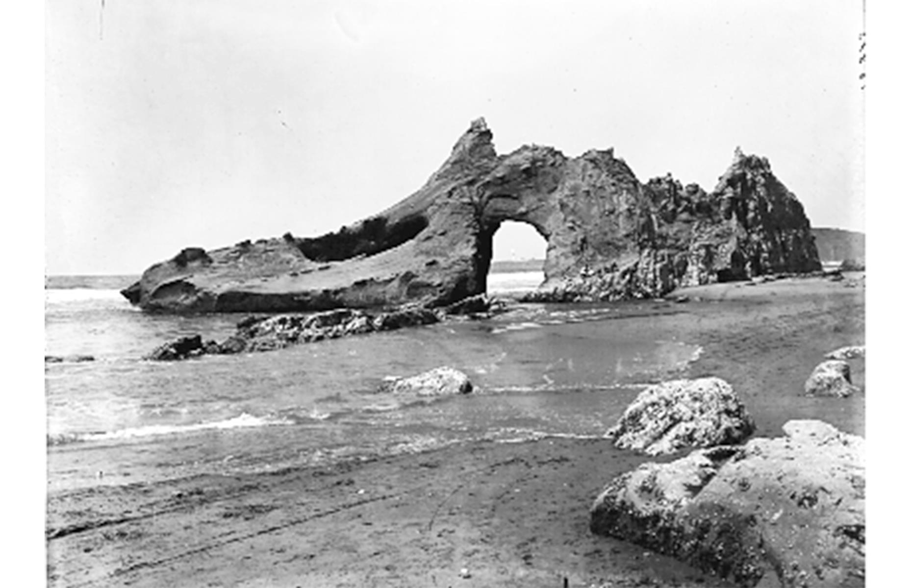 Slide 18 of 31: Jump-Off Joe is another natural Oregon landmark that didn't stand the test of time. The arching sea stack rose just off the shore at Newport's Nye Beach on Oregon's Central Coast and was a popular attraction in the 19th century. It's pictured here in 1910, a mere six years before it crumbled into the sea.