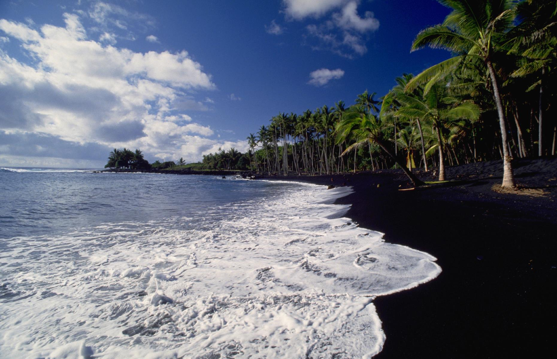 Slide 4 of 31: The Aloha State is known for its stunning black-sand strands and Kaimu Beach, on the Island of Hawaii, was one of the finest. Spreading over an eastern corner of the isle, its inky powder was hemmed in by palms and it drew tourists from across the country. This photo from 1985 shows the beach in all its glory. But, in the 1990s, this natural wonder was destroyed.