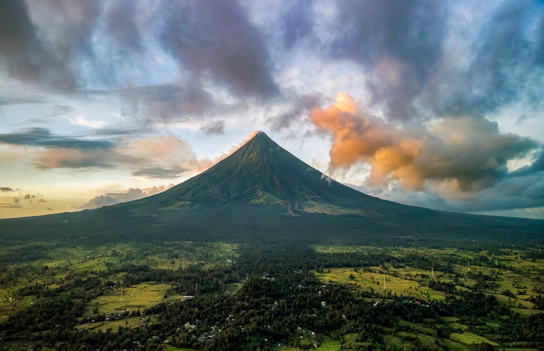 Slide 46 of 59: Famed for its iconic shape, many adore Mayon Volcano for being pleasingly symmetrical. Also known as Mount Mayon, the volcano is considered sacred to locals and stretches up 8,077 feet (2,462m). Frequently active, it last erupted in 2018 and is just as beautiful as it is powerful.