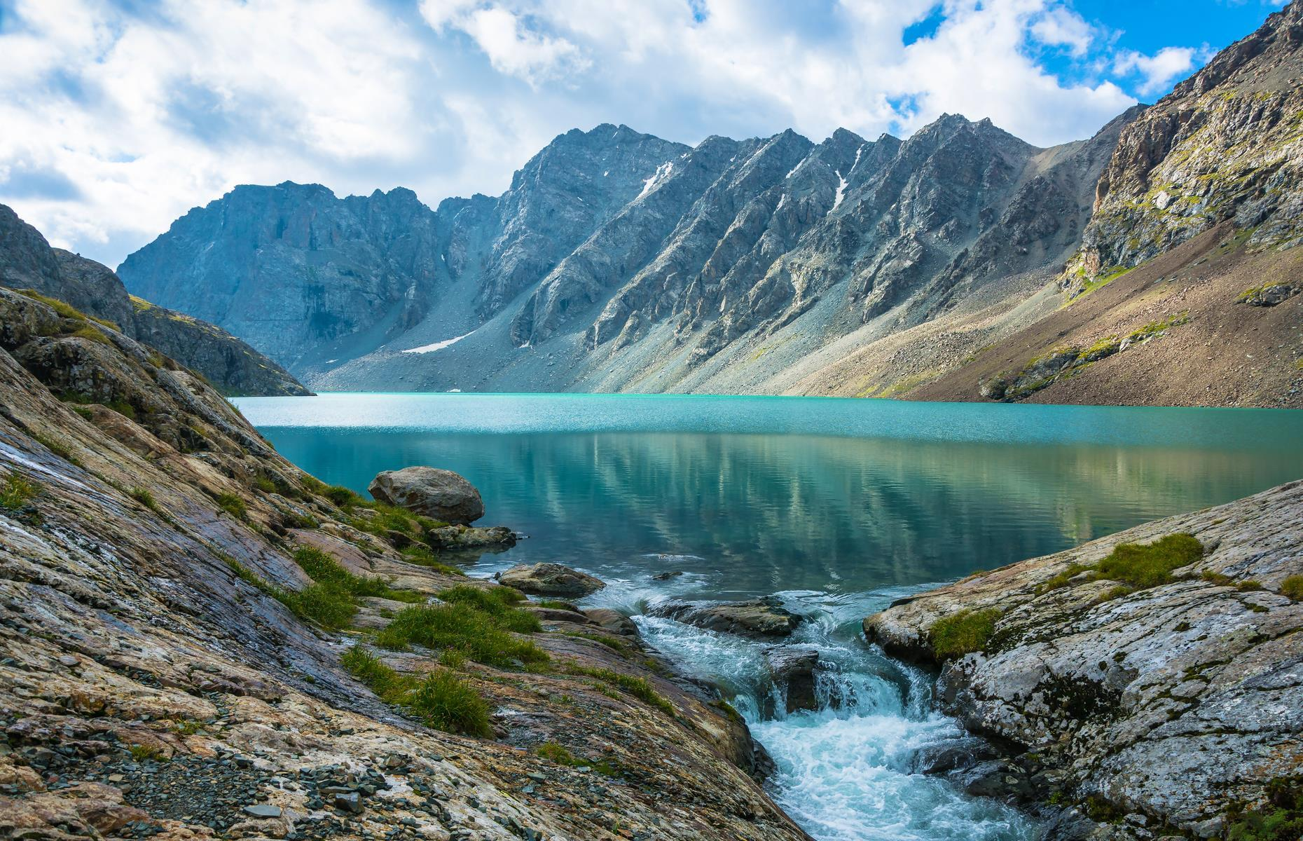 Slide 4 of 59: As far as lakes go, Ala-Kul is one of the world's most impressive. Nestled at an altitude of over 11,483 feet (3,500m) inside the Terskey Alatau mountain range in Kyrgyzstan, this stunning pool is one of the globe's natural gems. Enclosed by snow-capped peaks, the glacial lake covers just 0.5 square miles (1.5sq km) but its vibrant cyan waters are enough to entice and delight even the most jaded of explorer.