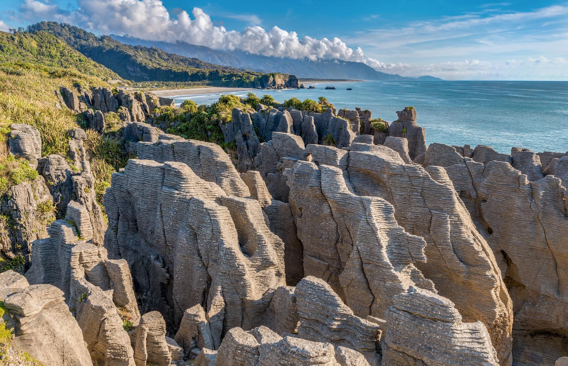 Slide 41 of 59: Situated inside Paparoa National Park on the west coast of New Zealand's South Island, the Punakaki Pancake Rocks are in a class of their own. These bulging limestone pillars were created 30 million years ago when dead marine creatures landed on the seabed. Immense water pressure solidified their fragments and earthquake activity slowly pushed the newly formed pillars upwards. Wind and seawater finally sculpted the rocks into the pancake-like structures we see today.
