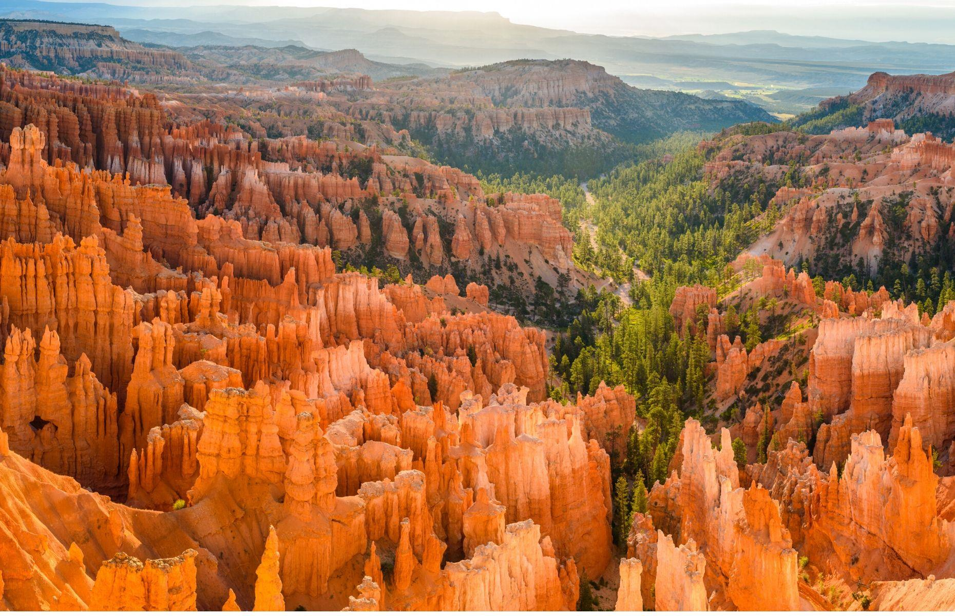 Slide 26 of 59: A demonstration of the power and beauty of nature, Bryce Canyon National Park is characterized by its crimson rock spires. Dynamic and distinctive, this canyon in Utah was formed by erosion over the course of about 15 million years. The hoodoos (the column-shaped rock formations) dazzle in shades of orange and red. Adventurous hikers can witness the surreal landscape for themselves by traversing the park's trails, ancient forests and natural amphitheaters.