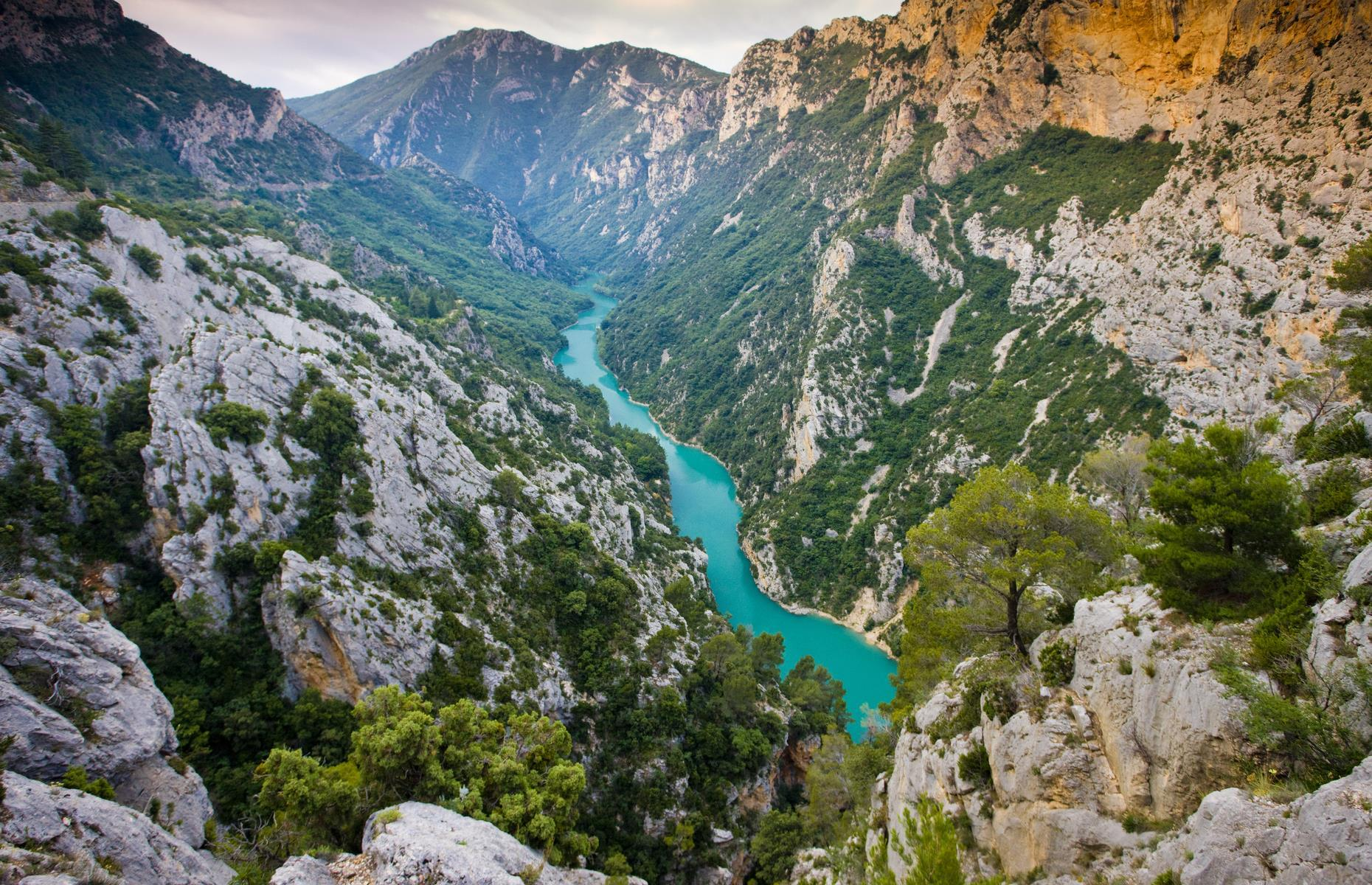 Slide 27 of 59: This theatrical limestone canyon appears to carry on endlessly into the horizon. Located in central Provence in southeastern France, the spectacular wonder dates back to the Ice Age. It was created when moving plates and glaciation shifted and melted the landscape to create the peaks and troughs we see today. Known as Verdon Gorge, the canyon takes its name from the French word for green and is famed for its lush forests and dazzling river that's almost too blue to be true.