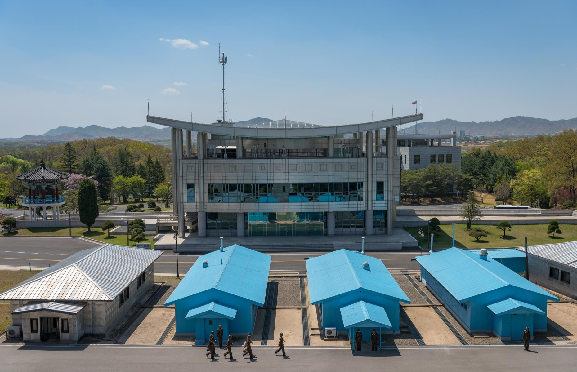Slide 4 of 51: The most well-known site of the DMZ and the closest point to North Korea, isthe JSA (Joint Security Area, pictured). Heresoldiers from both countries face each other with only a few feet of gravel in between, always ready to act in case of an emergency. In the JSA, negotiations between North and South Korea are held, with no negotiator having to leave theircountry, becausethe border runs right through the centerof the building and even the table the delegates sit around.