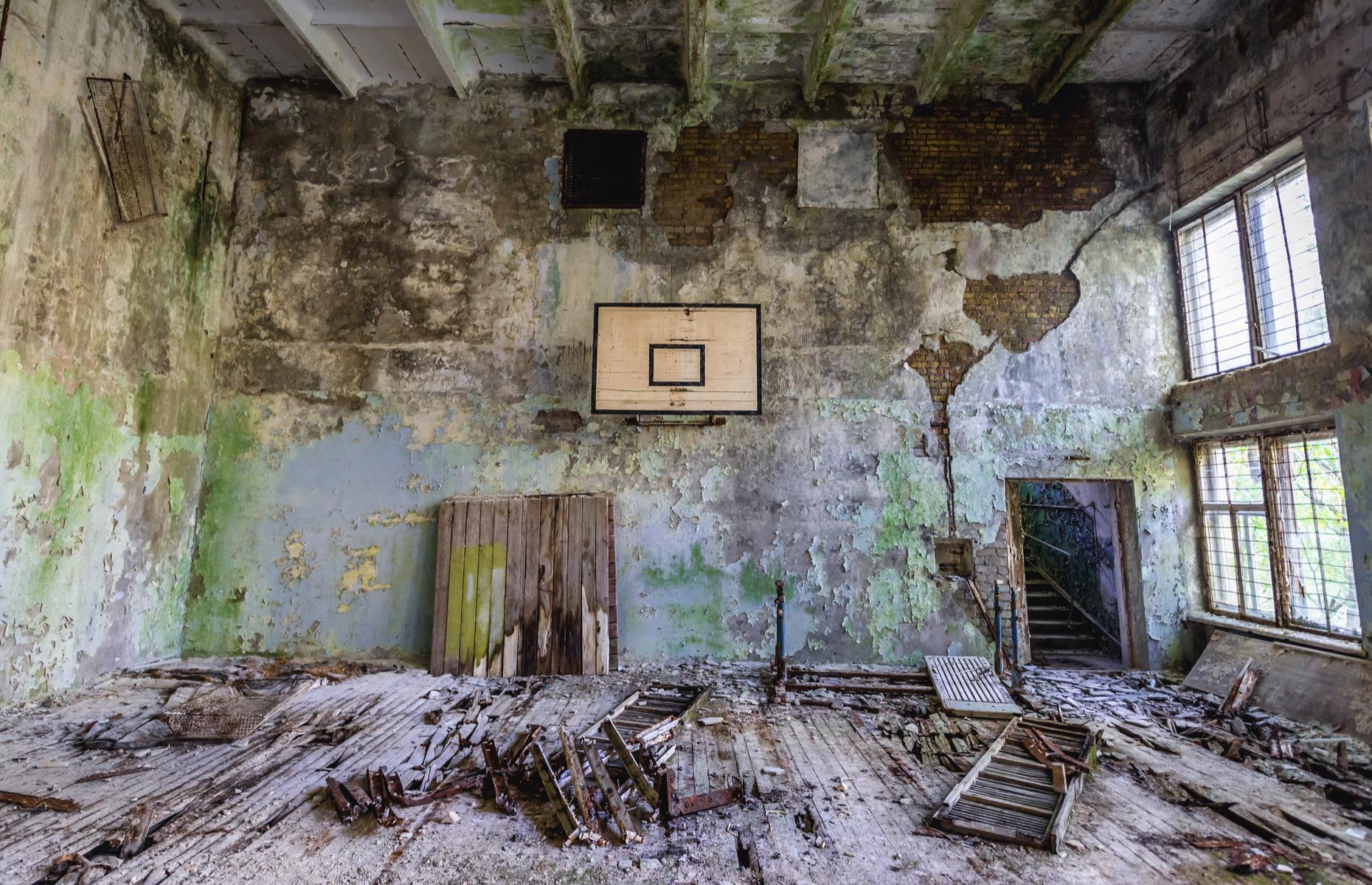 Slide 50 of 51: Crumbling walls, cracked wooden floors and parts of a basketball hoop are all that's left of this gym in the exclusion zone. The ruin is one of many abandoned buildings in the area.