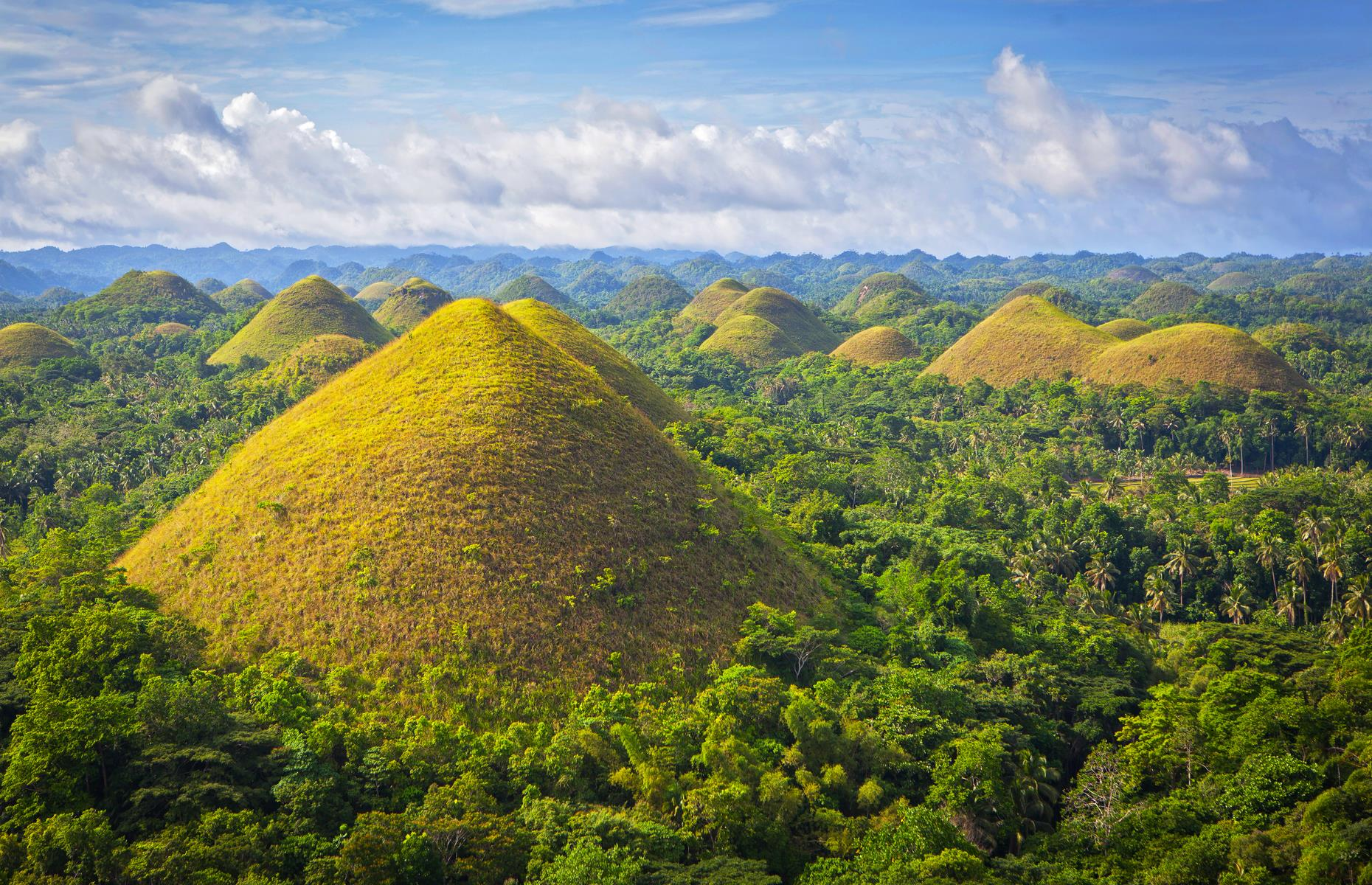Slide 31 of 35: The Philippines' conical Chocolate Hills – some of which soar to 394 feet (120m) – are another natural wonder oft explained by magic. One legend involves a pair of squabbling giants, who launched mud and boulders at one another until they were exhausted. Their tiredness led them to forget their bickering and the havoc they'd wrought too. They left behind the towering Chocolate Hills and wandered off into the sunset. Another story claims the hills are the dried tears of an amorous giant, who was mourning the death of his mortal love.