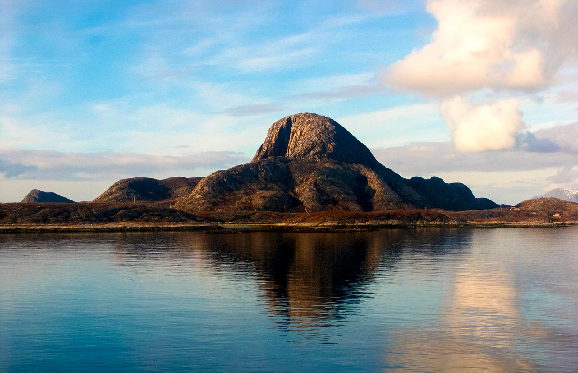 Slide 29 of 35: This hulking mountain, distinct for the gaping hole at its center, is steeped in folklore. Its story involves a troll, Hestmannen, who was chasing a beautiful woman, Lekamøya. As the path widened between them, Hestmannen became angry and shot an arrow intending to kill Lekamøya. However, the powerful troll king saved the day by throwing a hat into the arrow's path, saving the girl. The pierced hat purportedly turned into the mountain we see today, arrow hole and all. Typically you can visit the mountain on a moderate hike and even camp in its vicinity.