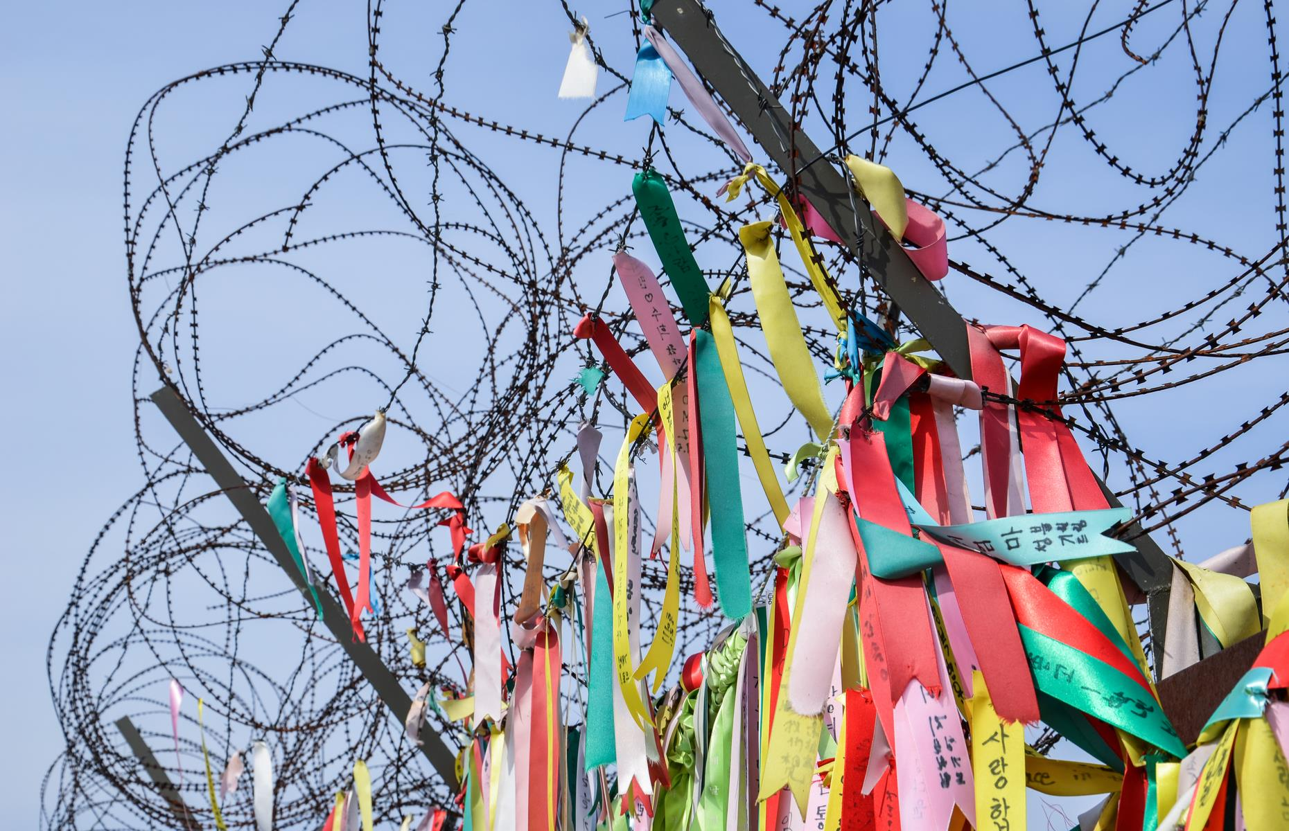 Slide 7 of 51: Civilians tied prayer ribbons to fences near the DMZ. Hopes for peace on the Korean peninsula have been rising since the latest summits between the countries' leaders and the USA.