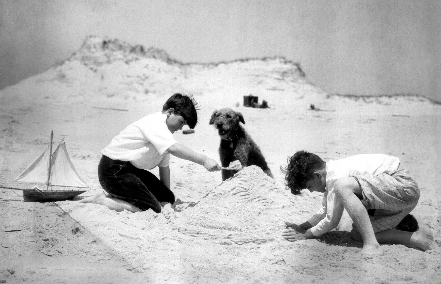Slide 27 of 35: The post-pandemic vacation looked similar in America too, with many families staying close to home during their leisure time, either by choice or due to financial constraints. This trio of beach-goers build a sandcastle on New Jersey shores in 1934. Take a look at more vintage snaps of family vacations throughout the decades.